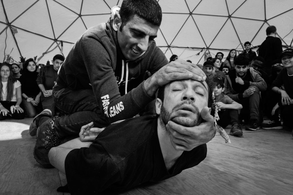 French breakdancer and choreographer Sofian Jouini (bottom) performs with another man during the March 3 Hope Show. Moments beforehand, Sofian had collapsed on the ground dramatically in the middle of a group performance. The crowd reacted by falling silent and clearing away from him while others, including the man pictured here, appeared to rush to his aid. For a time it was unclear whether this was part of the show, but slowly the man massaged, pulled, and prodded Sofian back to life. People watched rapt as the playfulness returned and Sofian's performed self was revived. (Photo by Annabelle Marcovici/GroundTruth)
