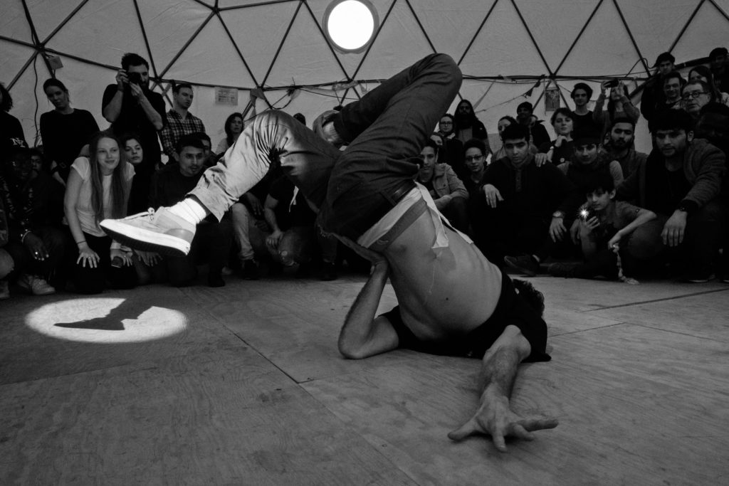 Visiting artist Sofian Jouini breakdances in The Dome during the March 3 Hope Show. (Photo by Annabelle Marcovici/GroundTruth)