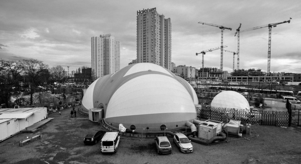The Dome theatre is visible to the right of La Bulle, the shelter for migrants run by EmmaŸs SolidaratŽ at Porte de La Chapelle in Paris's 18th arrondissement. Both structures are located in an old rail yard in the north of the city. Most of the migrants and refugees who are granted shelter here spent several nights sleeping on the streets in and around Port de la Chapelle before being allowed in, due to the limited space available in La Bulle's accommodation center. (Photo by Annabelle Marcovici/GroundTruth)