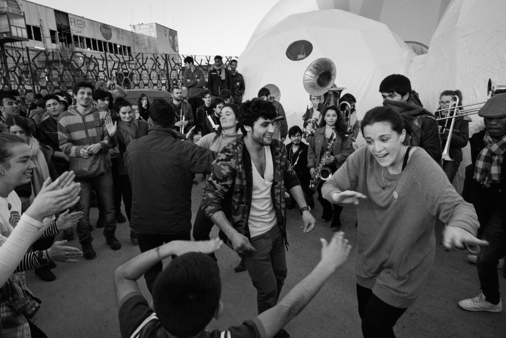 """Brass band Tyrassonores led Hope Show attendees out of the Dome, starting a brief dance party to conclude the show. Zmary Zahyre (center left), an Afghan man residing at La Bulle, dances with Italian visiting curator Elisa Giovanetti (right) and a young boy. Elisa's role as visiting curator involved bringing in artists to lead workshops, but as with virtually everyone else involved in Good Chance, she also wore many other hats with less official titles. """"My special skill is loving people,"""" she replied, laughing. (Photo by Annabelle Marcovici/GroundTruth)"""