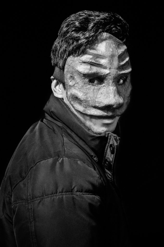 """Arifullah """"Arif"""" Fana — a 27-year-old Afghan man living at La Bulle — wears a mask he made in a Good Chance workshop. Arif, who speaks six languages, came to Good Chance's workshops nearly every day. """"I was a Thaï boxing teacher back in Afghanistan,"""" he said. """"In the dome, I have been able to give some Thaï boxing lessons and it felt great."""" (Photo by Annabelle Marcovici/GroundTruth)"""