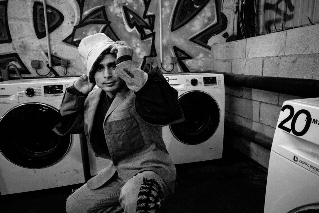 Faiz Mohammad Bashardot, an Afghan man staying at La Bulle, poses next to a washing machine inside La Bulle's accommodation center. (Photo by Annabelle Marcovici/GroundTruth)