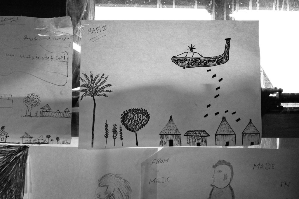 Drawings by workshop participants, children and adults alike, cover the wall and window space of Good Chance's cramped office space in La Bulle. The theater sometimes holds workshops on drawing and other 2D art, but paper and art supplies are nearly always available in the small dome for anyone who wants to draw. (Photo by Annabelle Marcovici/GroundTruth)