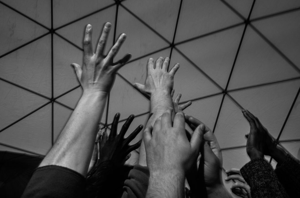 Participants in a contact improvisation workshop in Good Chance's larger Dome gather close together and reach skyward, forming a single, collective gesture with their bodies. (Photo by Annabelle Marcovici/GroundTruth)