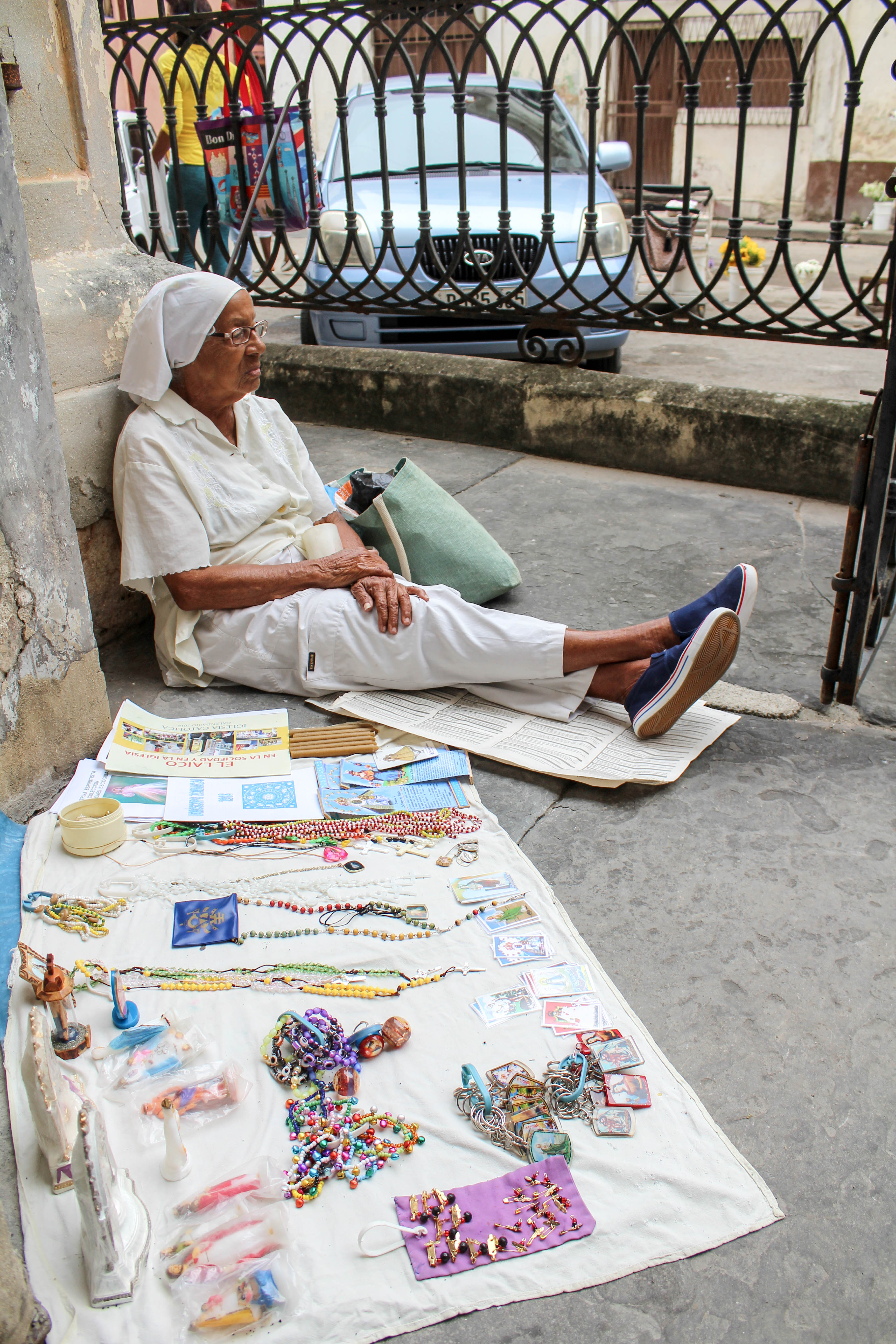 Regla Valdez, 88, sits outside the front doors of Our Lady of Mercy Church on May 24 to sell various items pertaining to Santería worship. Valdez, who has been selling these objects for 50 years, said she chose the church because of how popular it is. In years past she said she was told to leave the church stoop, but lately that has not been the case. (Photo by Paxtyn Merten/The GroundTruth Project)