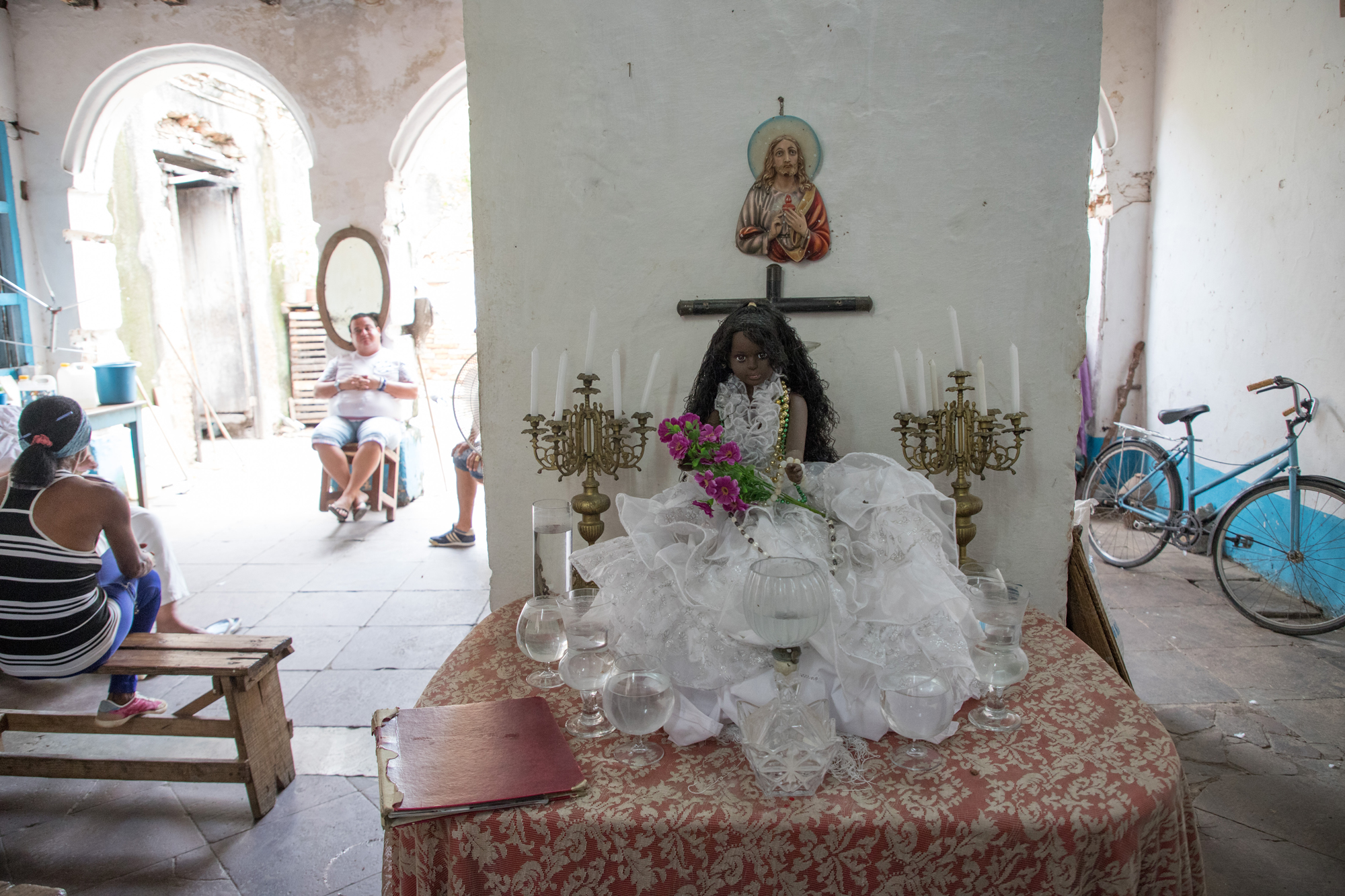 A doll representing Obatalá, the parent of all orishas, sits on a table in a Santería temple in Trinidad. Obatalá is identifiable for being dressed in all white and is syncretized with the Catholic Saint Mercedes. (Photo by Riley Robinson/The GroundTruth Project)