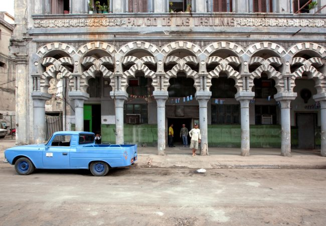 A man stands on the street next to a vintage car in Cuba. (Photo by Falkenpost/Pixabay)