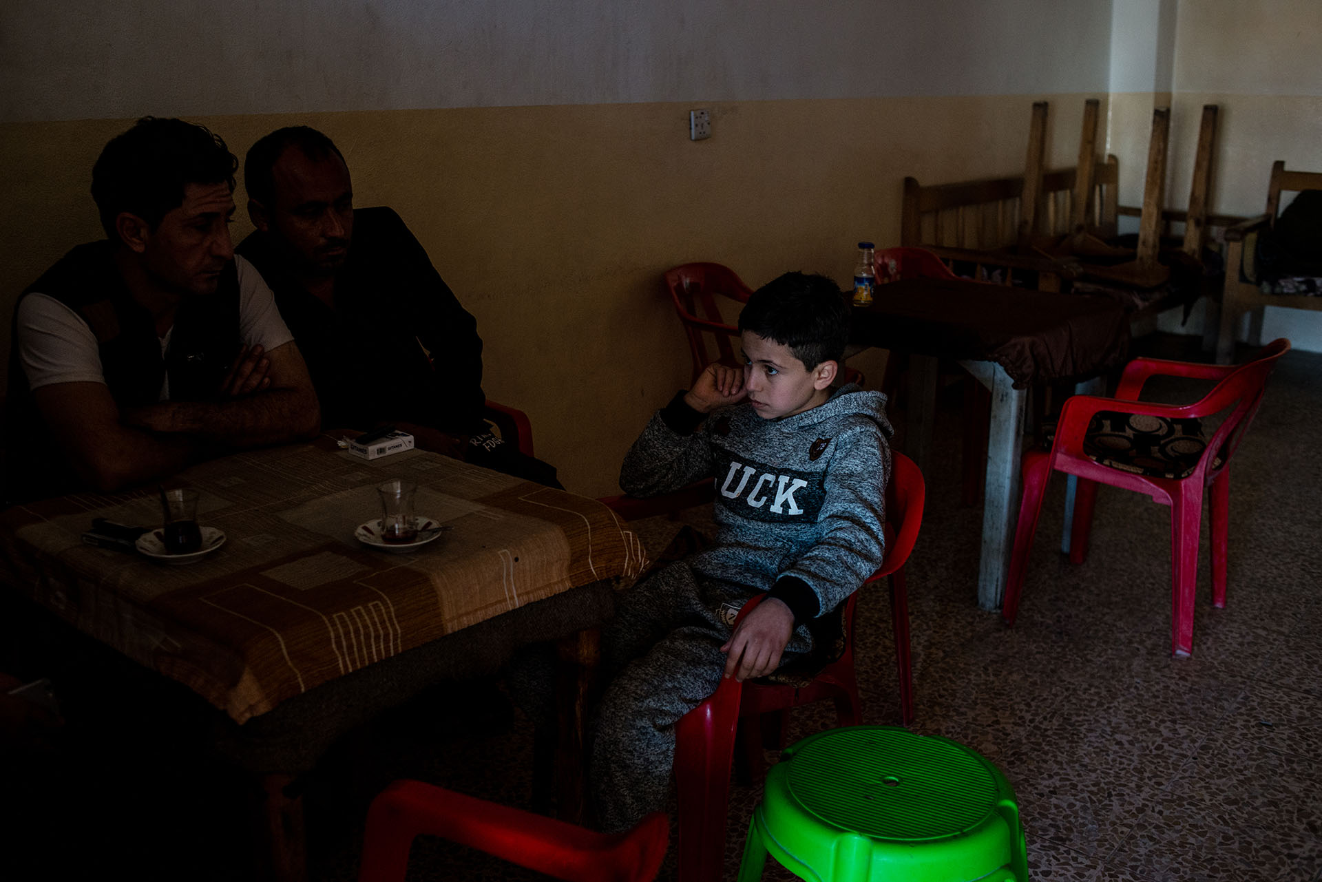 Dilshad sits in a cafe with his father and a family friend. He was recently released from ISIS captivity after his family bought him back. (Alex Potter/GroundTruth)