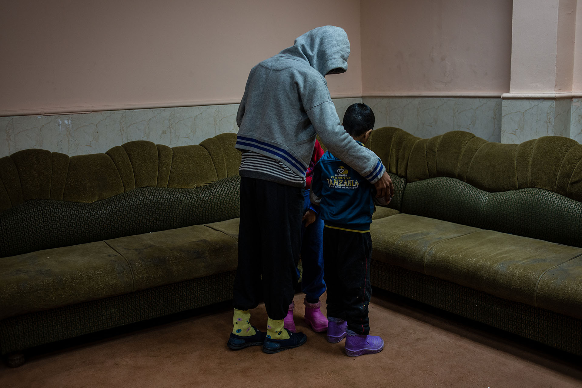 Two disabled boys, found wandering around playground city alone, are shielded by an older resident at the Mosul orphanage. (Alex Potter/GroundTruth)