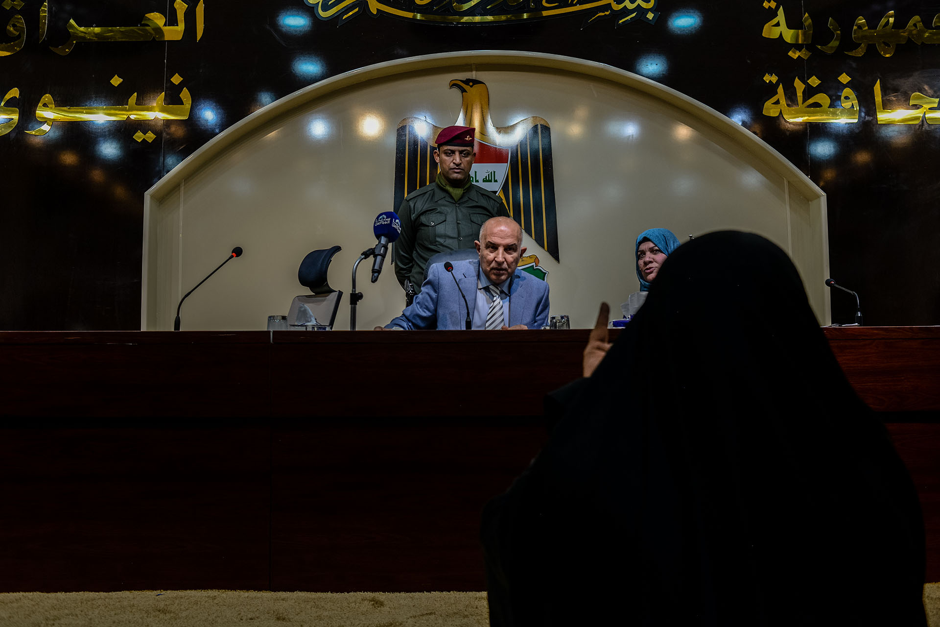 Mosul Governor Nofal Hammadi holds a public meeting to hear the concerns of citizens, and speaks to a widow who is asking for financial support.  (Alex Potter/GroundTruth)