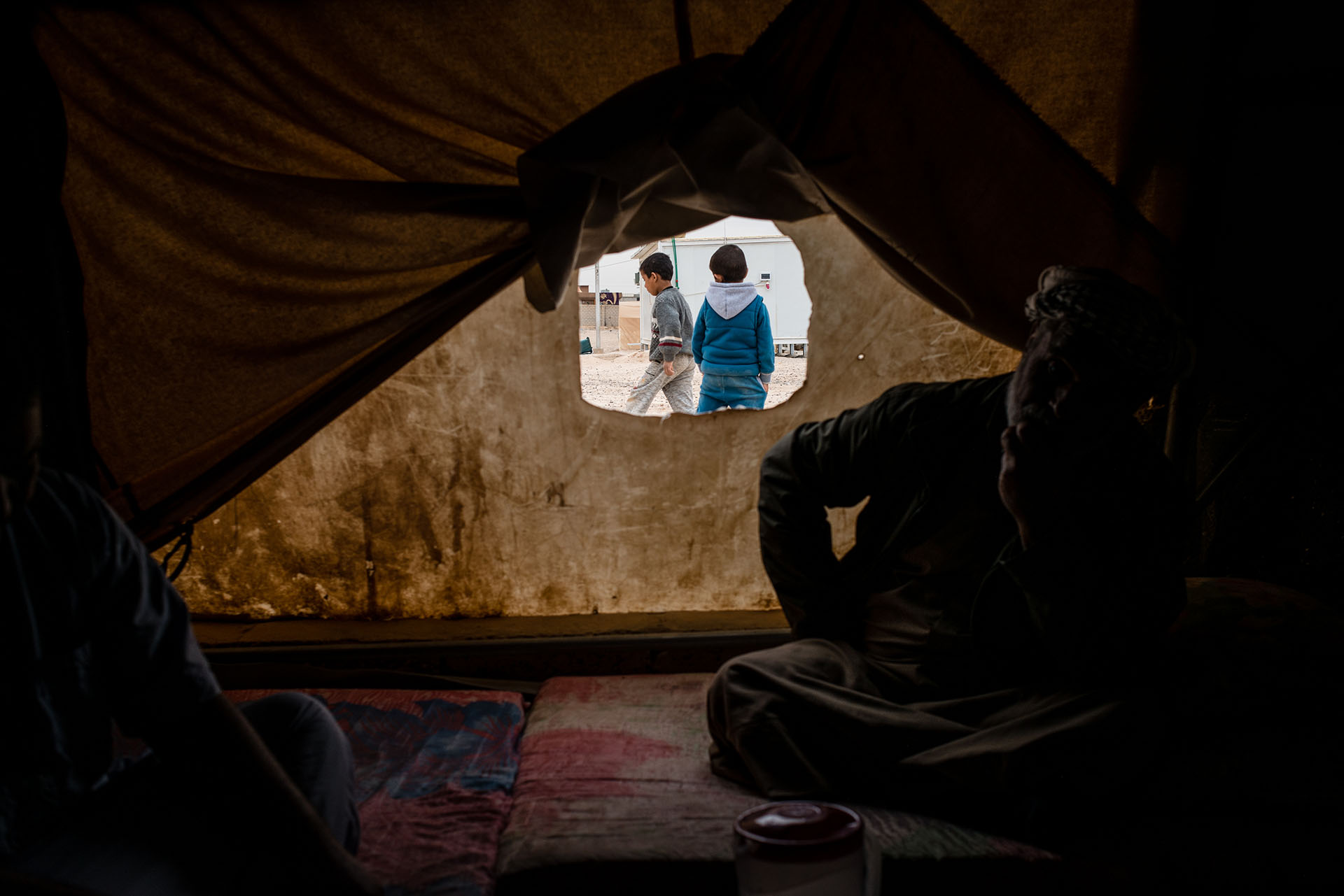 Young boys play outside a tent in Shahama camp, a settlement that holds families with direct or suspected ties to ISIS. (Alex Potter/GroundTruth)