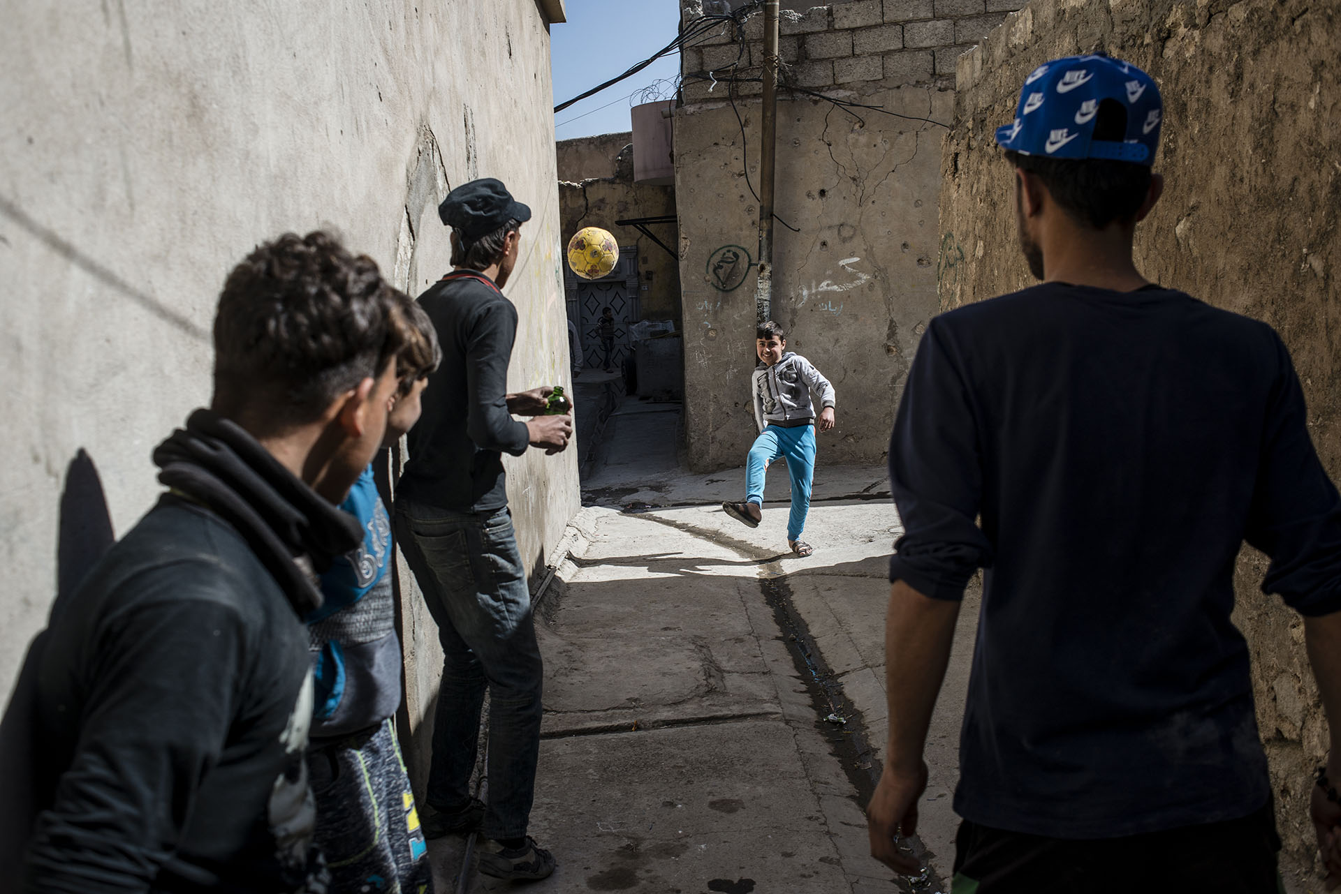 Ali, a boy who lost his arm in a mortar strike while his family was displaced, plays with his friends in the Old City once again.  (Alex Potter/GroundTruth Project)