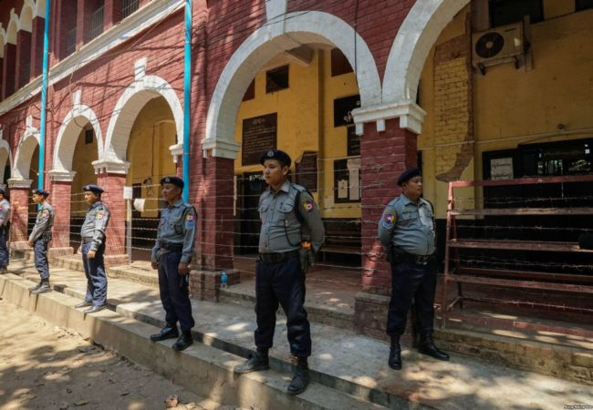 Myanmar Police officers stand on guard outside a courtroom in Insein Township during Wa Lone and Kyaw Soe Oo's trial.