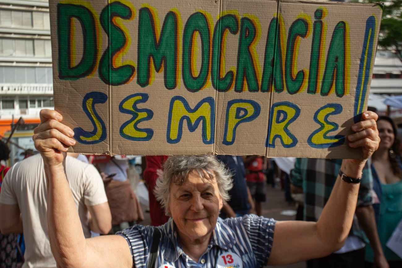 """""""Democracy always,"""" says the sign held by a protester in a Carnival demonstration against Bolsonaro that gathered thousands in São Paulo on October 27, one day before the runoff. (Photo by José Cícero da Silva/GroundTruth)"""