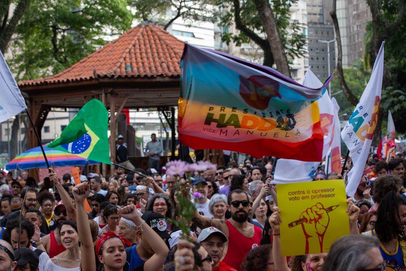 """A Carnival demonstration against Bolsonaro gathered thousands in downtown São Paulo one day before the runoff. Using colorful clothes, with their faces painted with glitter, protesters danced and sang """"not him"""", """"no step back"""" and """"dictatorship never more"""" in upbeat samba melodies. (Photo by José Cícero da Silva/GroundTruth)"""