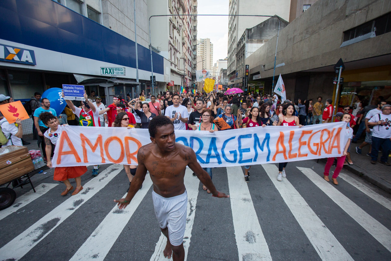 """""""Love, Courage, Joy,"""" said the banner carried by protesters in a Carnival demonstration against Bolsonaro that gathered thousands in São Paulo on October 27, one day before the runoff. (Photo by José Cícero da Silva/GroundTruth)"""