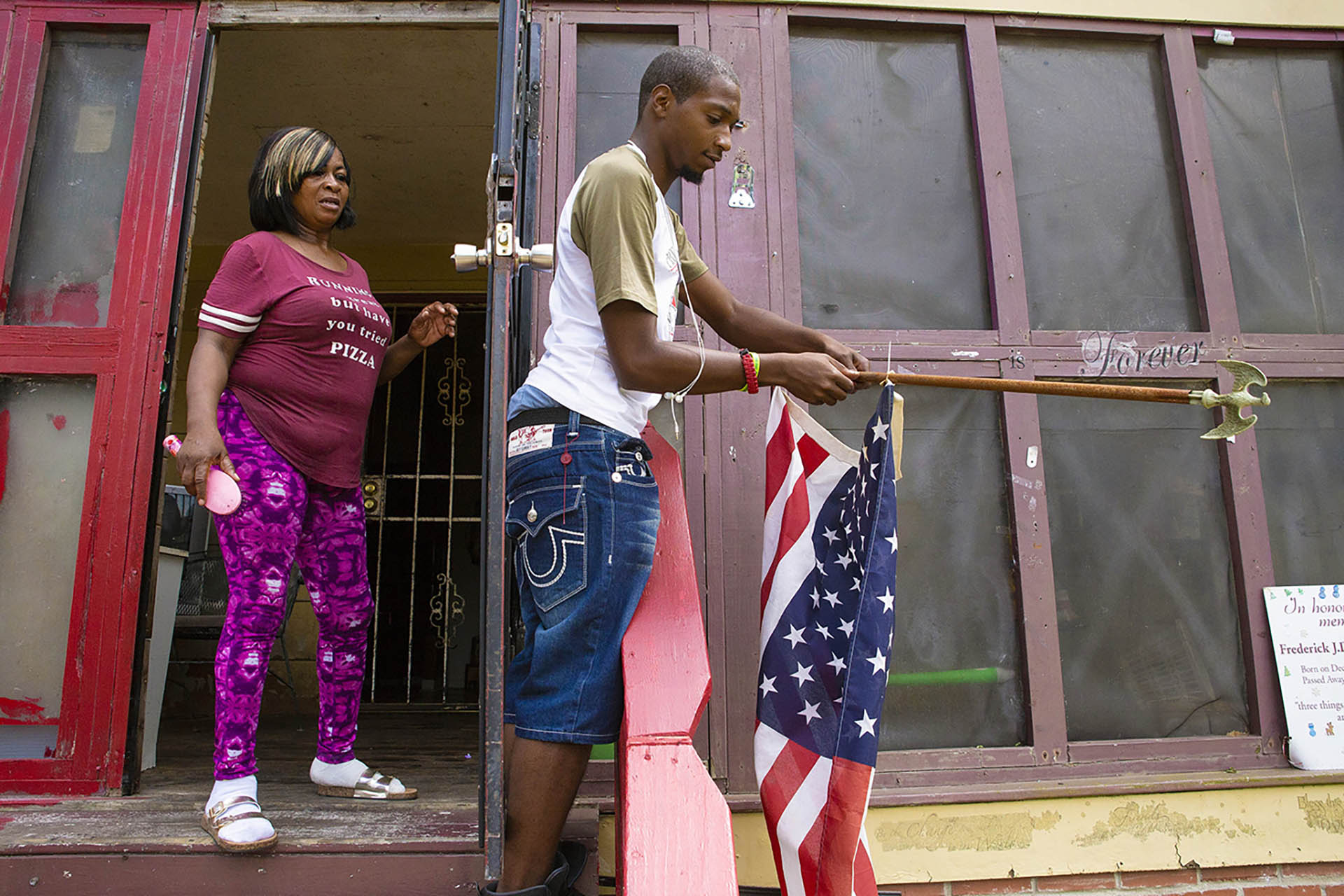 Marilyn Martin, left, assists her nephew, Lee Eric Evans, as he hangs a U.S. flag outside of Maritn's home on Davis Street in Jackson, Miss. Tuesday, July 3, 2018. (Photo by Eric J. Shelton/GroundTruth)