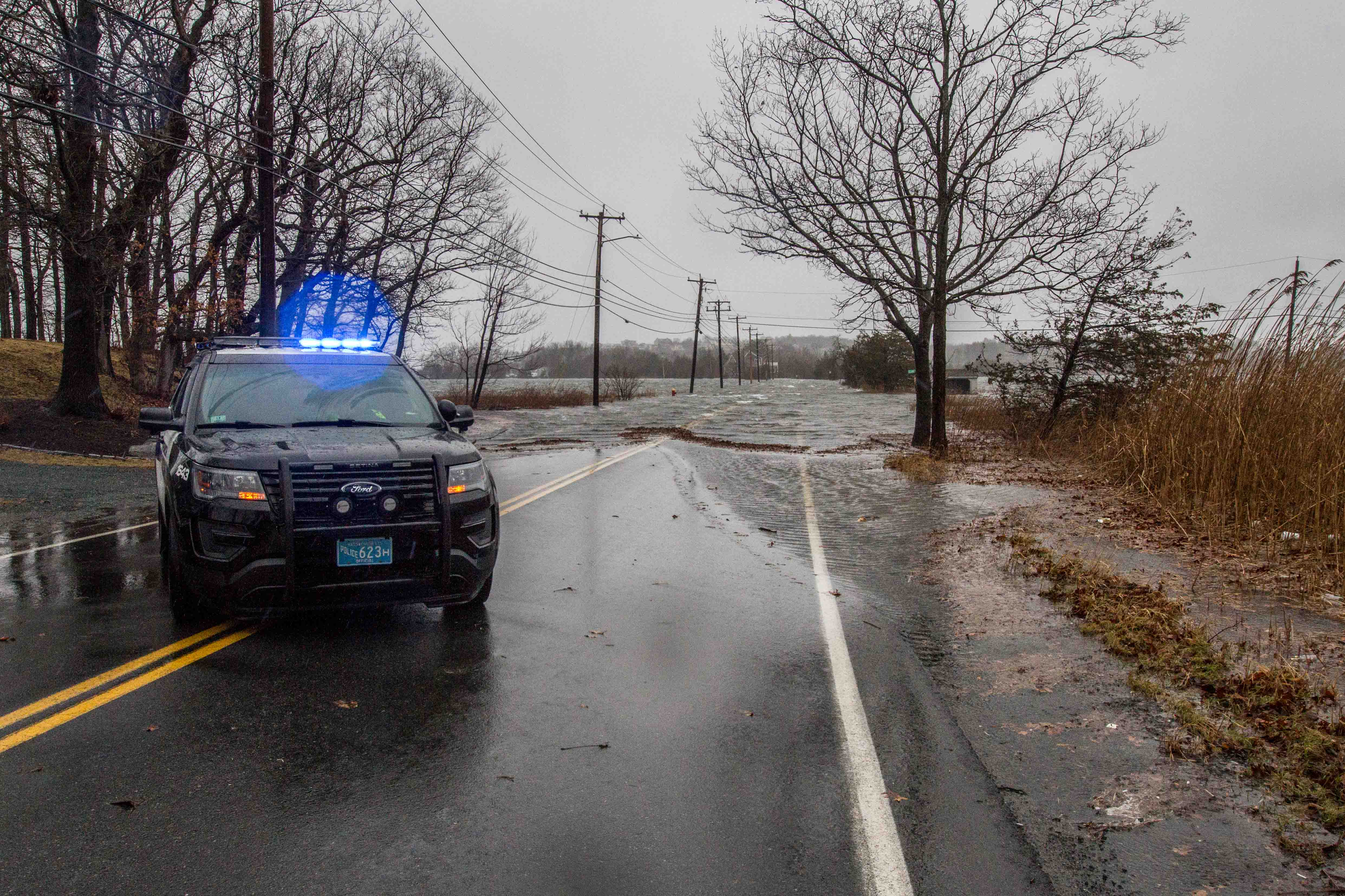 A powerful winter storm on March 2, 2018, pushes tide waters high enough to drown a road across the Great Marsh, temporarily cutting off hundreds of households at the far end from essential services in Ipswich. A healthy marsh can help protect coastal residents by softening the force of surging tides and heavy surf. (Photo by Coco McCabe/GroundTruth)