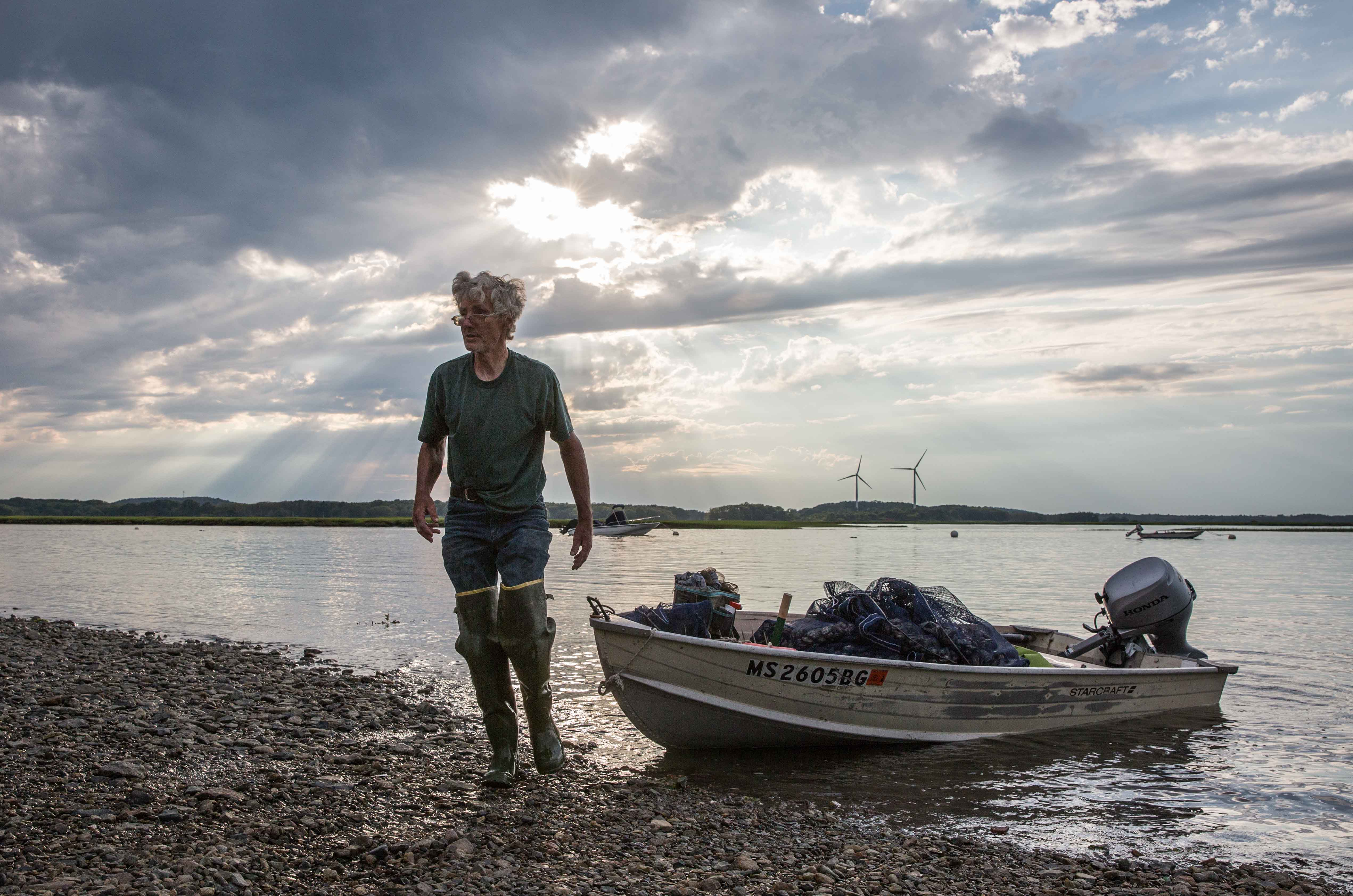As the ocean reclaims the creeks and mud on a summer evening, clammer Russell Fowler, Jr. returns to shore with his haul. He says the clam flats in the Great Marsh are the best office he's ever worked in. In Ipswich, a commercial clamming permit costs $450, which a good digger can reportedly earn back in a day. (Photo by Coco McCabe/GroundTruth)