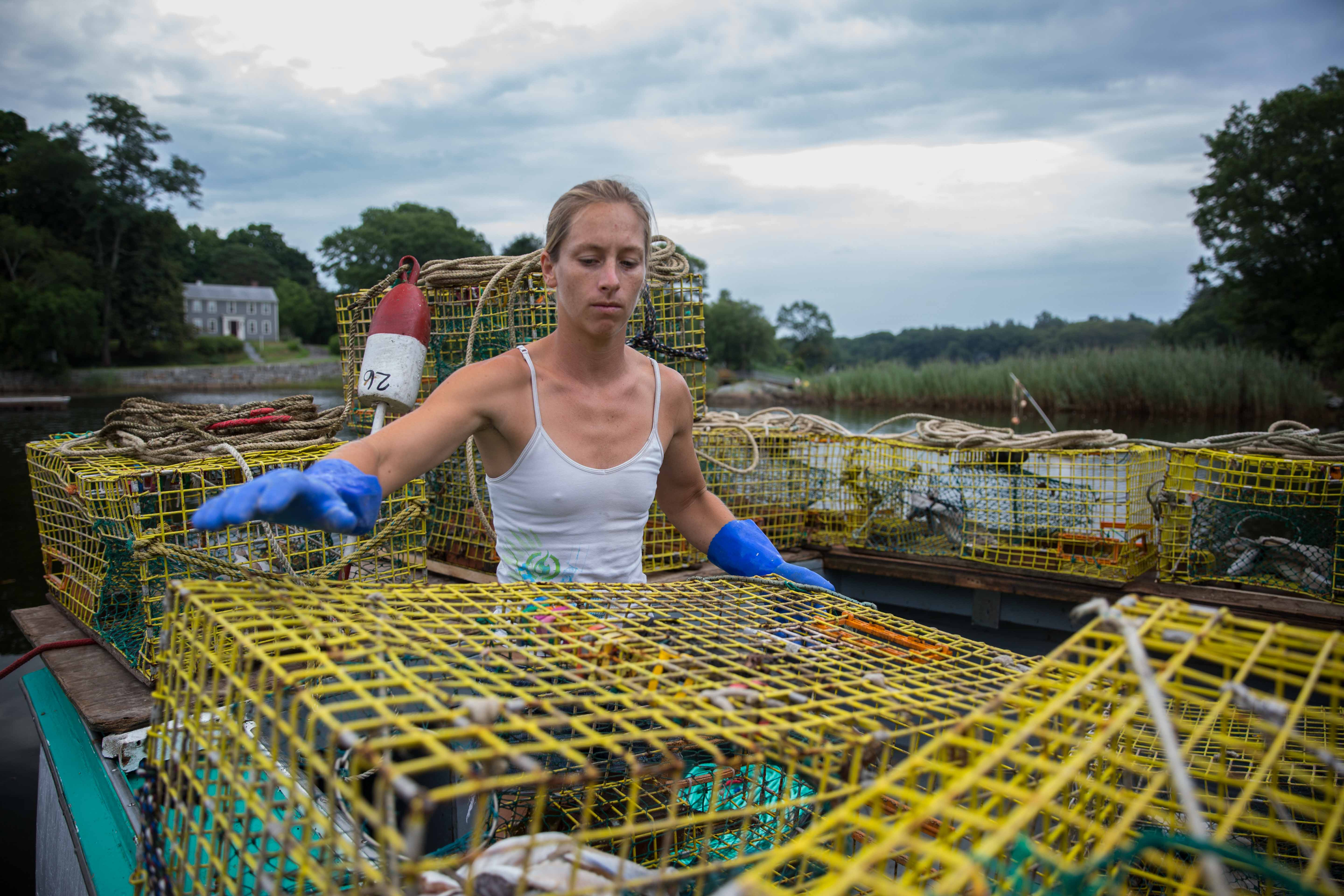 Rachel Munsell loads bait fish into lobster traps aboard the Loan Shark. The boat is docked in the Ipswich River estuary, part of the Great Marsh. Munsell spends six months of the year lobstering with her stepfather, who owns the boat. (Photo by Coco McCabe/GroundTruth)