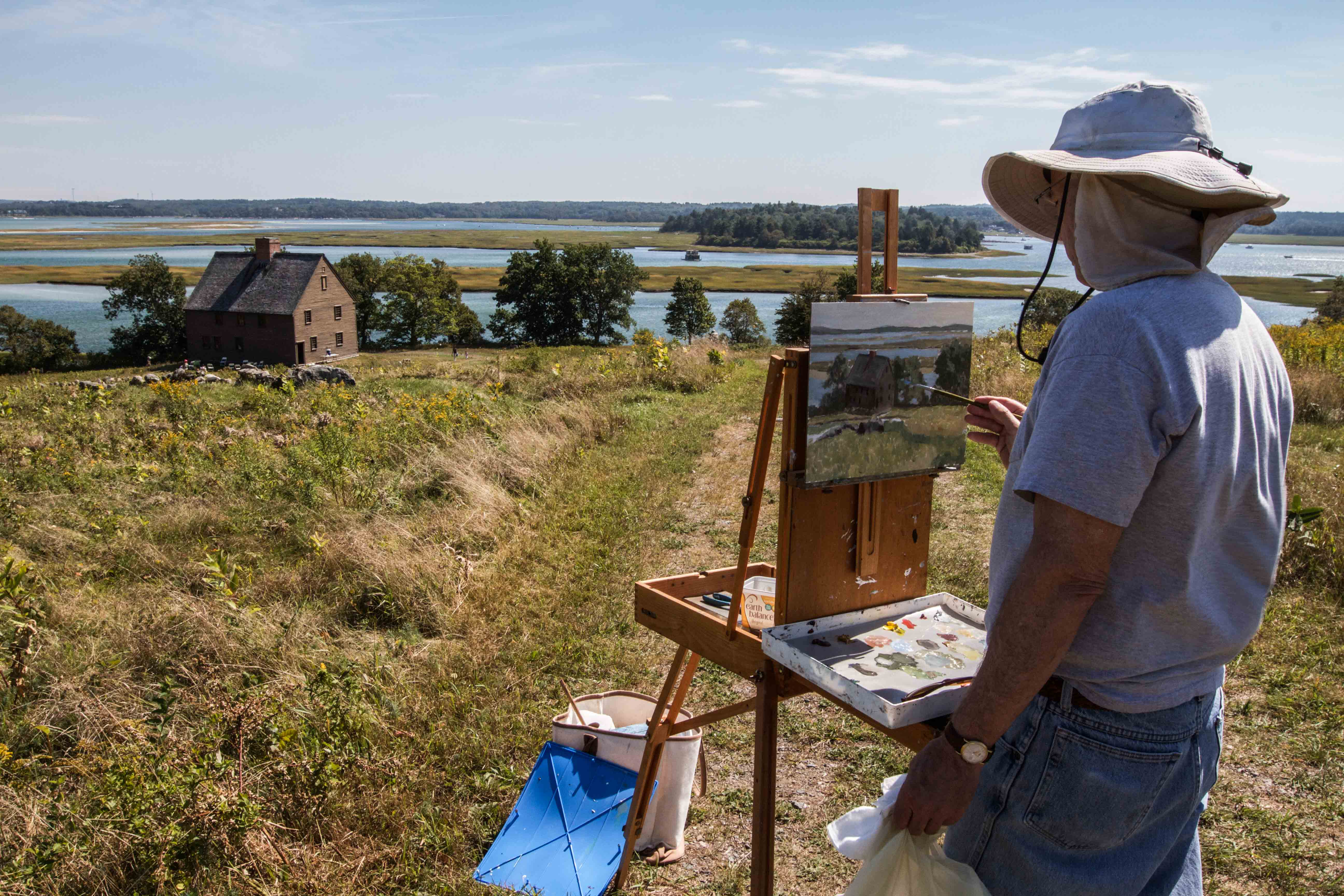 A plein air painter on Choate Island, a 135-acre preserve in the Essex River estuary, captures the Choate House, which was built more than 250 years old. The island was the setting for the 1996 movie The Crucible. Based on the play by Arthur Miller and starring Daniel Day-Lewis, the movie is a fictionalized account of the Salem, Mass., witch trials in the early 1690s. (Photo by Coco McCabe/GroundTruth)