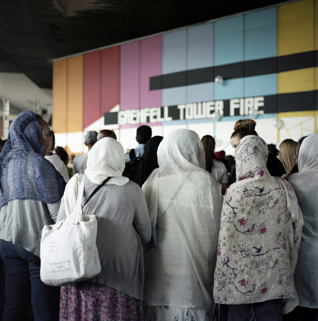 Local residents of the North Kensington community gather round the Wall of Truth, located under the West Way, dedicated to families and survivors of the Grenfell Fire. (June 14th, 2018).