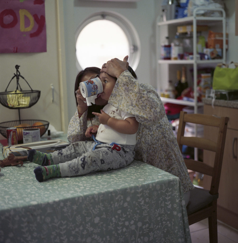 Tarek Gotti's wife and son Maddox in the kitchen of their home in Henry Dickens Court Estate.