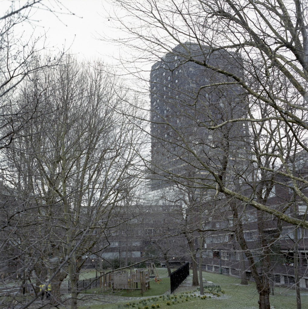 The skeletal remains of Grenfell Tower stands behind the Lancaster Estate, whose occupants still grieve over the loss of their friends and family who perished in the fire.