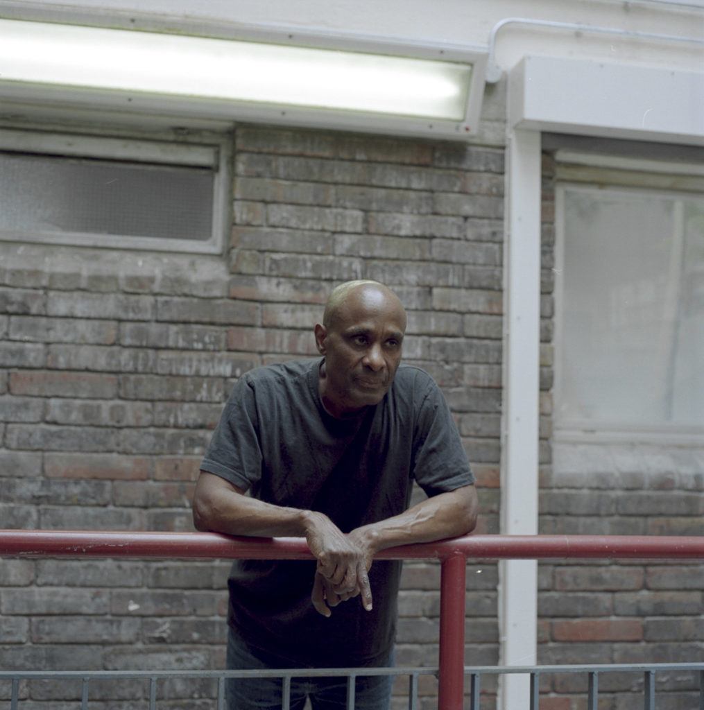 Joseph Alfred of Hurstway Walk Lancaster Estate W10, Resident for over 40 years. stood in the halls of his housing block. The Lancaster Estate stands immediately next to Grenfell Tower, and parts of the estate were badly damaged from the fire. The residents there were one of the first to see the beginnings of the fire - trying to signal to their Grenfell neighbours to come down from the top floors. Joseph lost a close friend who lived in the highest levels of the tower block.