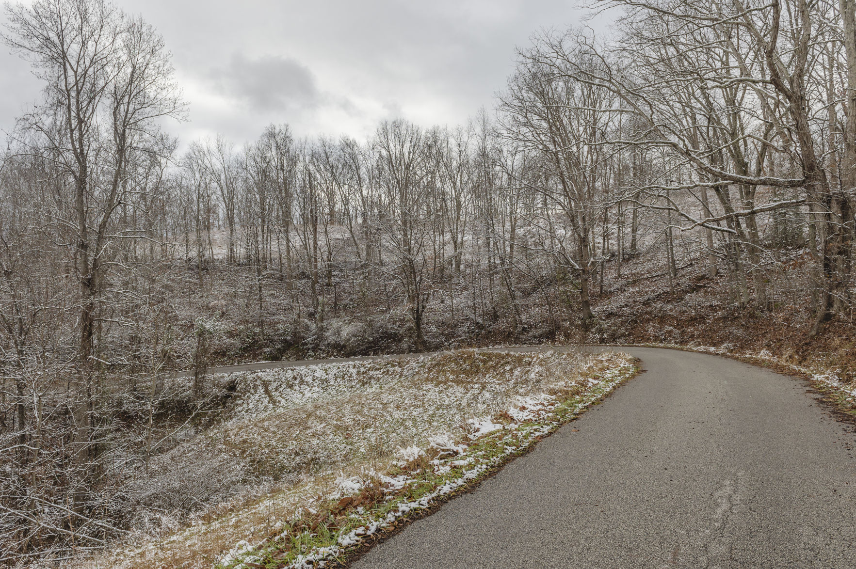 Allen Adkins and his brothers and sisters live off this curve in Harless Fork Road, in Lincoln County. Adkins remembers his father thought he'd die before seeing a paved road cut through the hollow. Today, Adkins wonders if he will feel the same about water service. (Photo by Craig Hudson | Gazette-Mail)