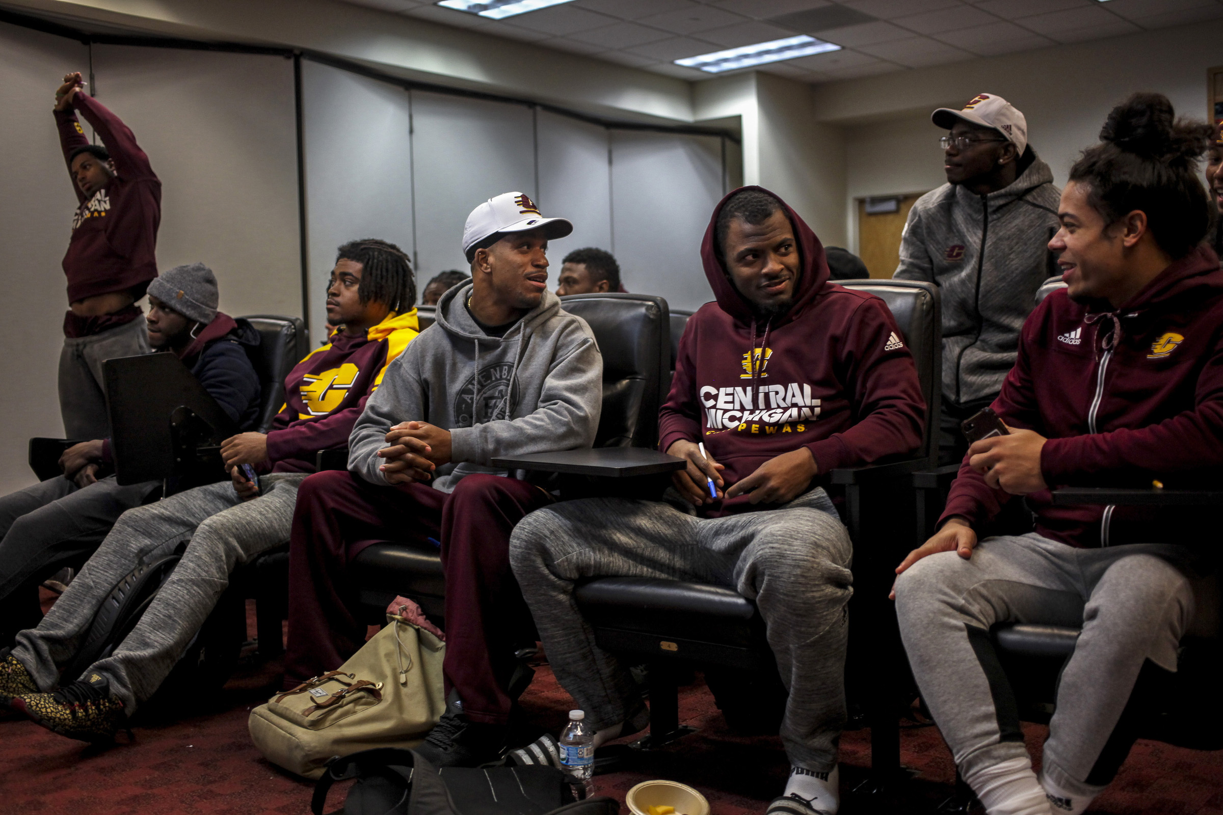 "Before an early morning practice, Ray Golden, Jr., talks with his teammates on the Central Michigan University football team. As a defensive back, Golden takes his responsibility to his team serious and refers to football as his ""job."" Because of the long hours spent with his team, the football team is a second family for Ray. (Photo: Josephine Norris/GroundTruth)"