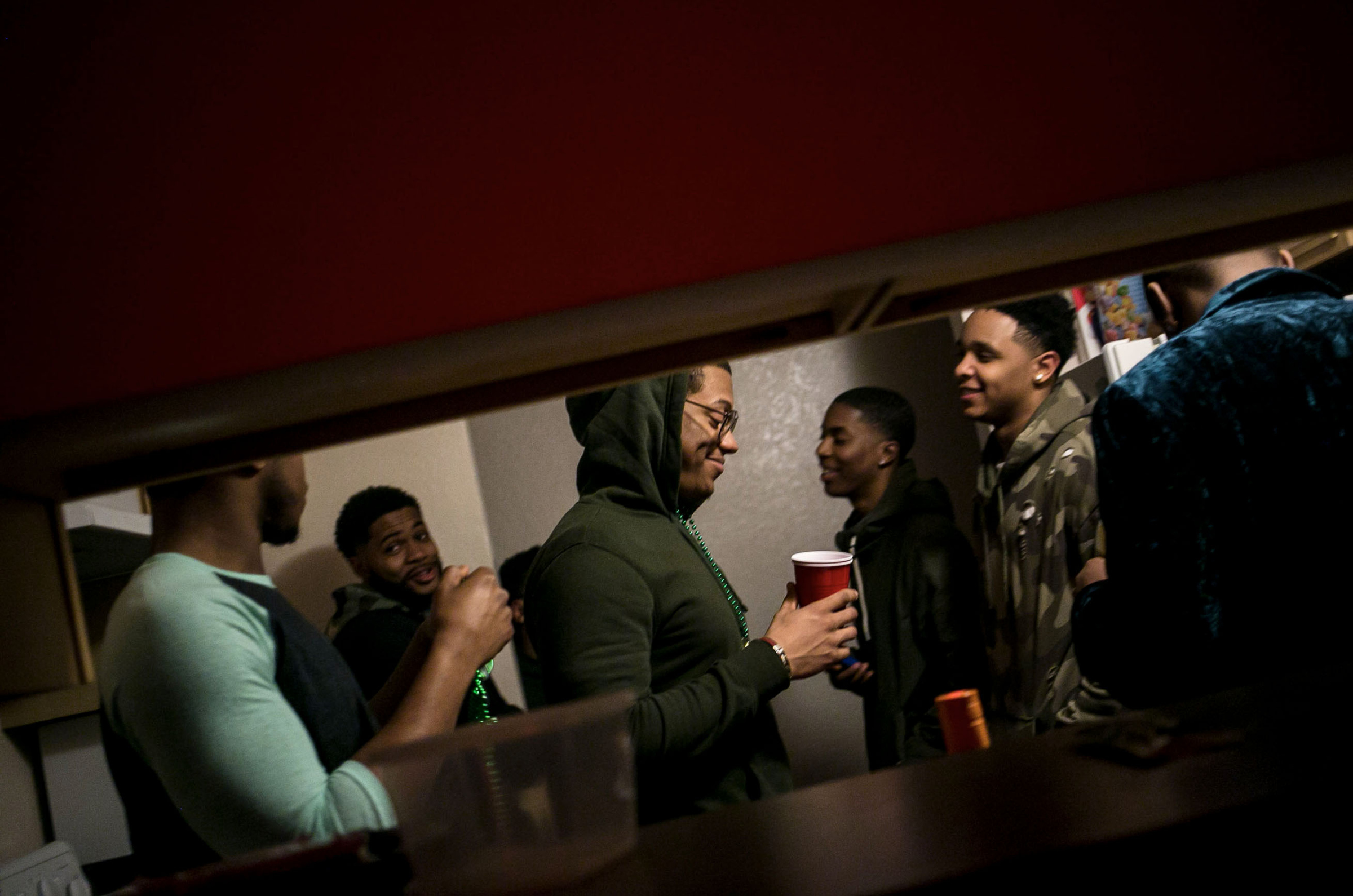 During a party for his 21st birthday Trenton Carson smiles to himself as he is surrounded by his fraternity brothers of Kappa Alpha Psi. (Photo: Josephine Norris/GroundTruth)