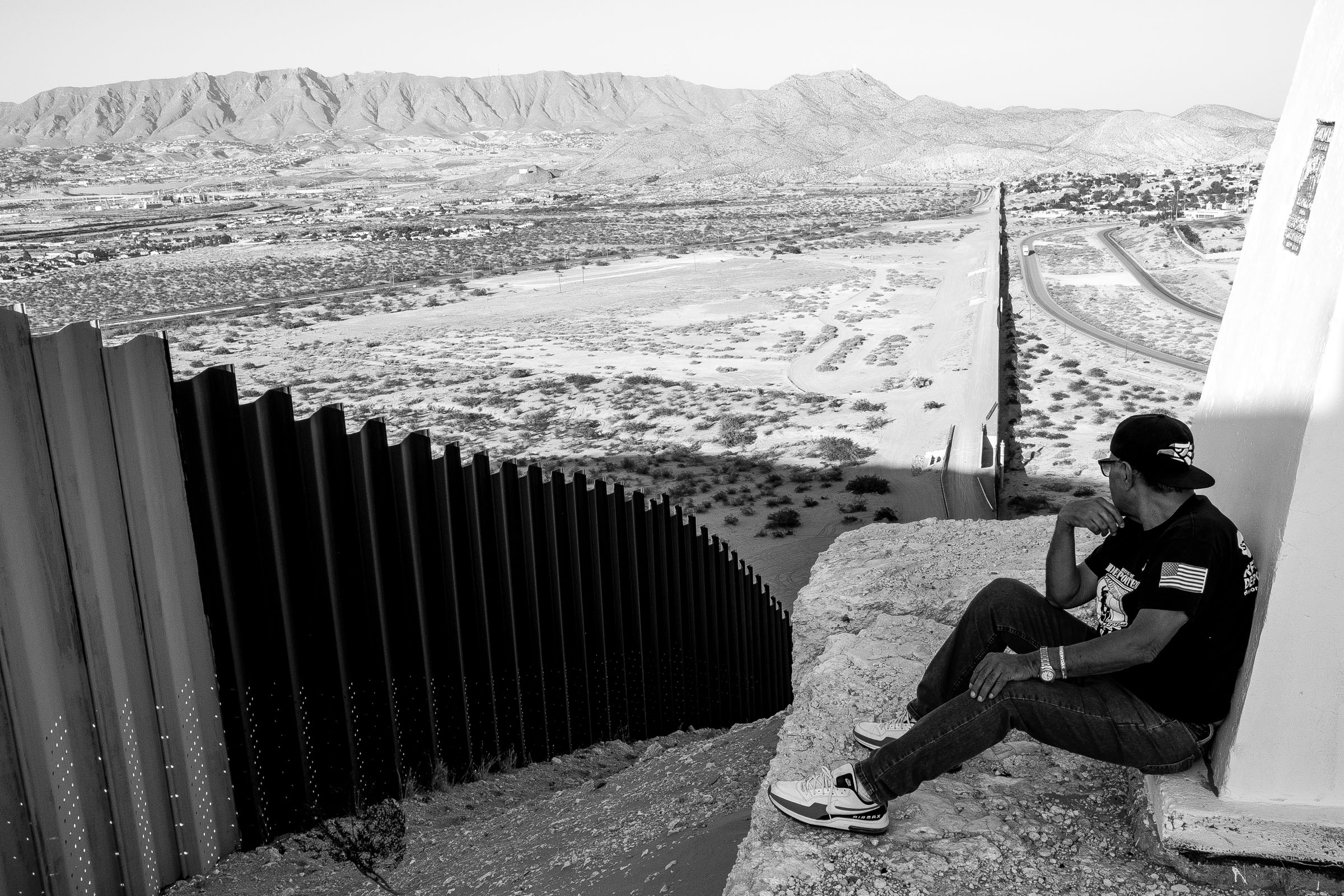 Deported U.S. Army veteran Jose Francisco Lopez Moreno, 73, overlooks the fence separating him from the United States as he sits along a hill in Ciudad Juárez, Chihuahua, México, Monday, July 23, 2018.   Lopez Moreno was drafted to the U.S. Army during the Vietnam War in 1967. He deployed to Vietnam from 1968 to 1969 serving in combat even though he did not speak a word of English. Latino veterans in his unit would translate for him during his time in the service. He was assigned to work in transportation and at night he would be on guard duty at a helicopter base in Vietnam where he also performed rescue missions when helicopters were shot down.   Twenty six years after his military discharge, Lopez Moreno was arrested in a hotel room in Wichita Falls, Texas. He was caught purchasing cocaine from a police officer and was charged with intent to purchase and distribute narcotics in 1995. He was sentenced to nine years in prison and served eight years behind bars with a one year reduction for good conduct. In 2003, he was deported to Mexico because the crime he was sentenced for is considered an aggravated felony—a deportable offense for a green card holder. (Photo by Joel Angel Juárez/GroundTruth)