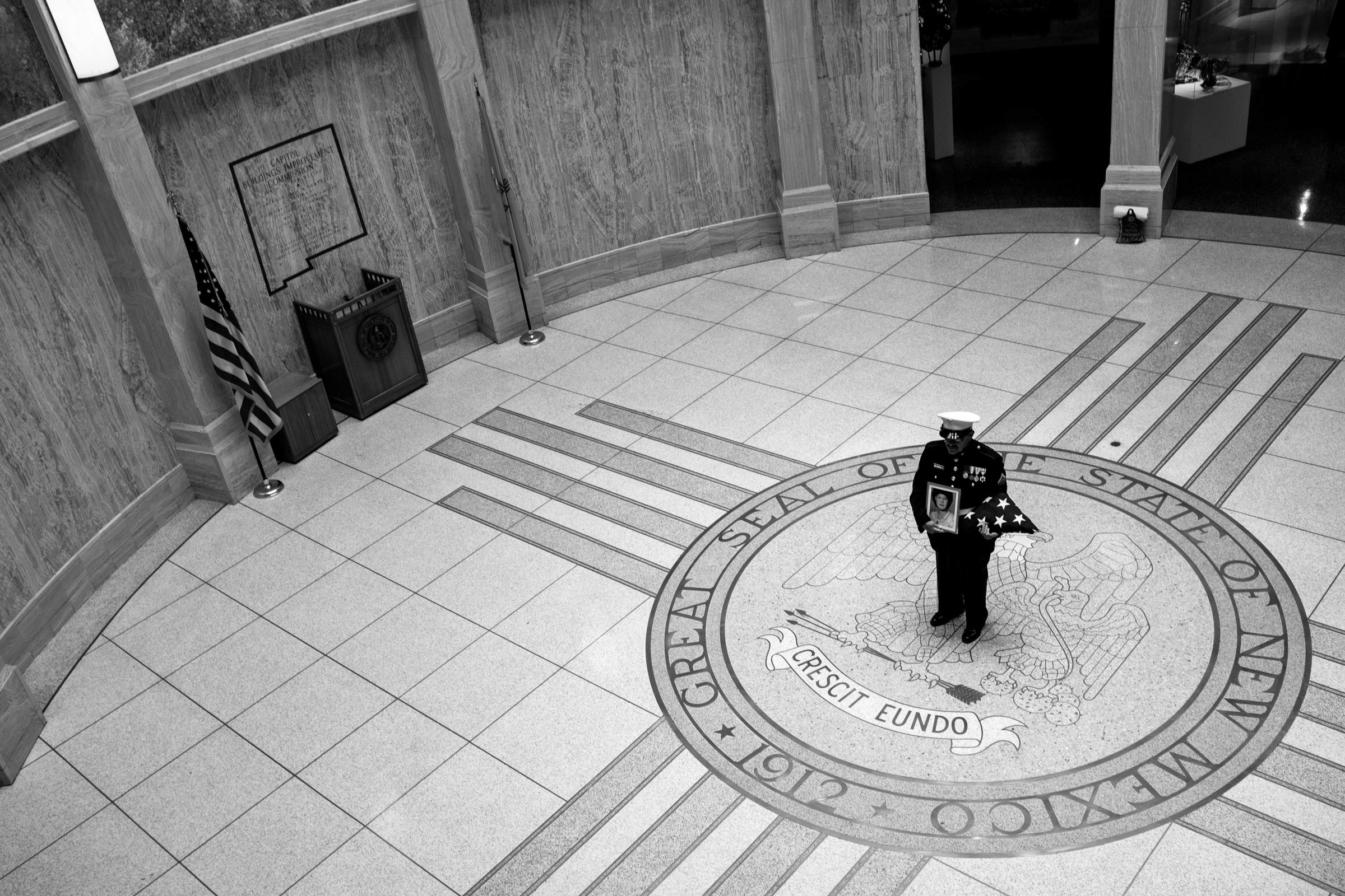 U.S. Marine Corps and Vietnam War veteran Manuel Valenzuela stands on the rotunda floor of the New Mexico State Capitol Building as he holds an American flag and a framed photograph of his mother in Sante Fe, New Mexico, Monday, Sept. 24, 2018.   Valenzuela and his older brother Valente, a U.S. Army and Vietnam War veteran, have been fighting deportation since 2009 for misdemeanor offenses which they completed sentences for. Their birth certificates classify them as resident aliens since their mother, a native from New Mexico, gave birth to them in México. Their deportation cases have been lingering in the courts. They might qualify as U.S. citizens as a result of their mother's citizenship status. (Photo by Joel Angel Juárez/GroundTruth)