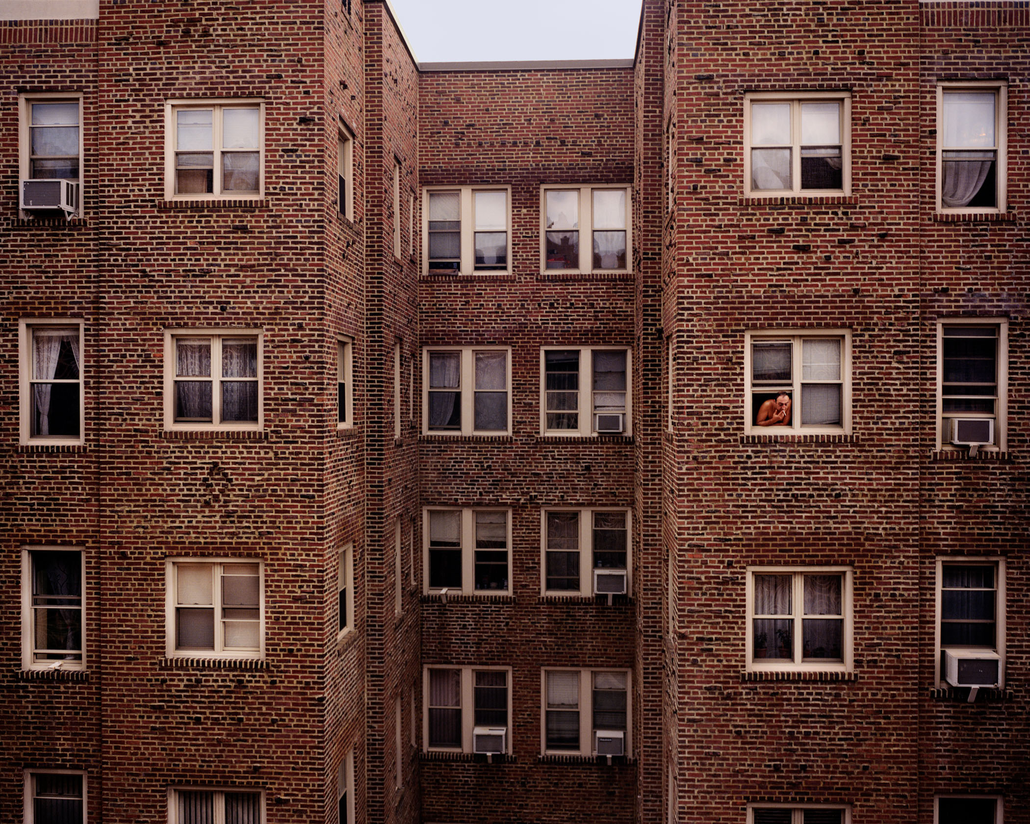 A man enjoying a cigarette out of his apartment window. (Photo by Alexey Yurenev/GroundTruth)