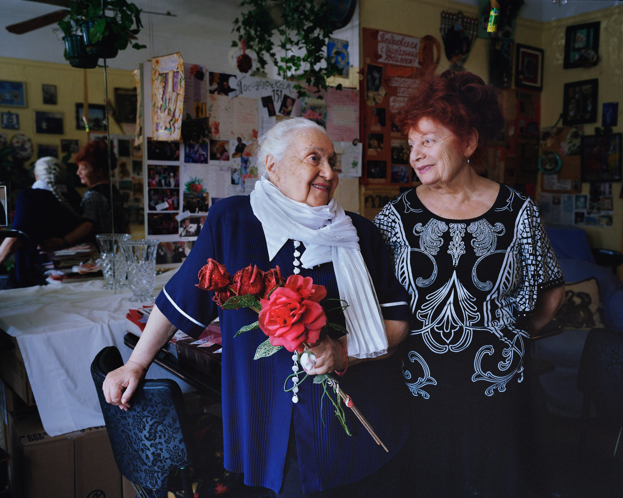 Vera Hatsernova (left)  and Anna Malkina (right), in Hatsernova's living room. Hatsernova is known for her salons and Malkina volunteers with veterans. (Photo by Alexey Yurenev/GroundTruth)