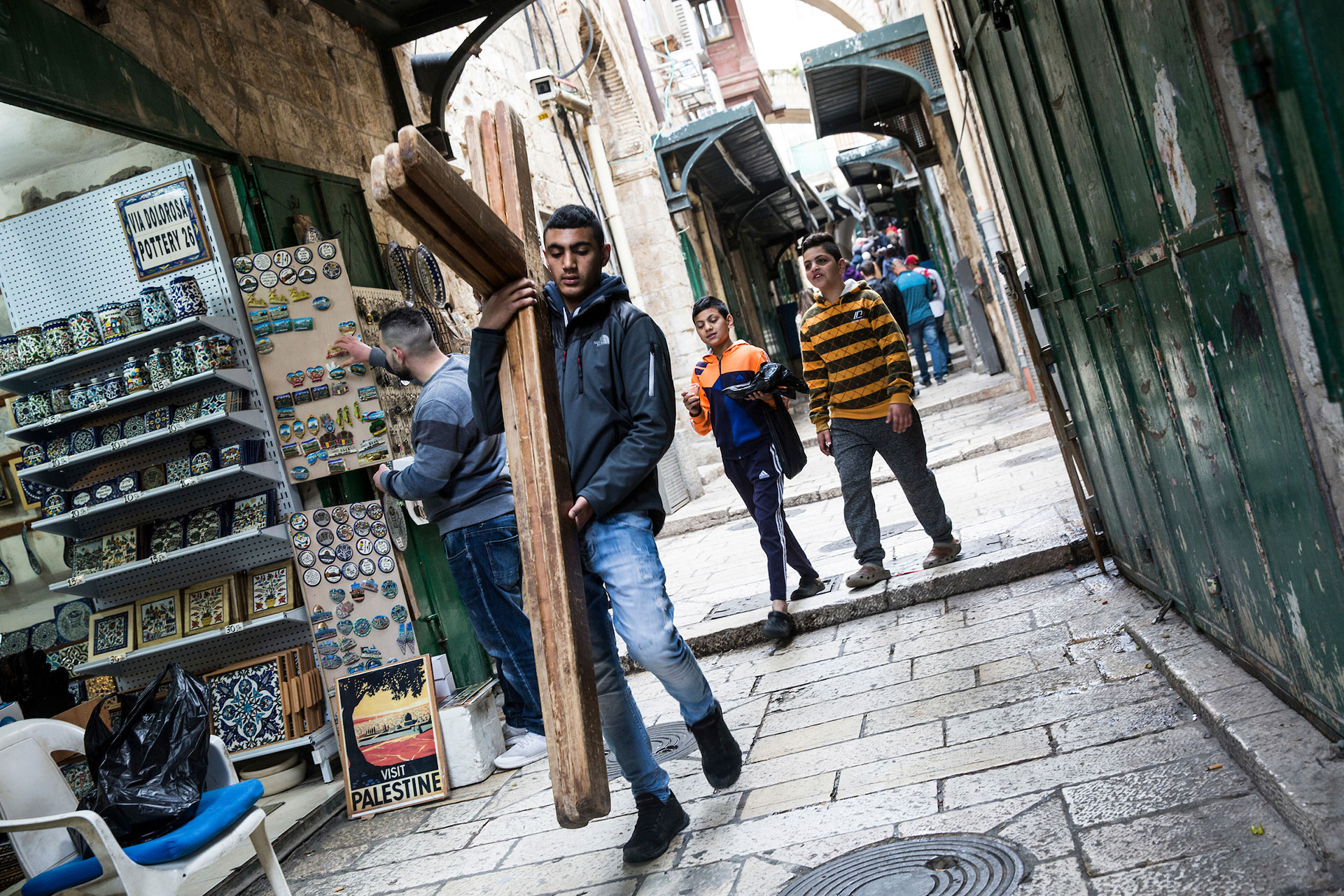 A Palestinian walks carries wooden crosses along the Via Dolorosa for the Christian worshipers during the Good Friday procession in Jerusalem's Old City on March 30,2018.(Photo by Heidi Levine for The GroundTruth Project)