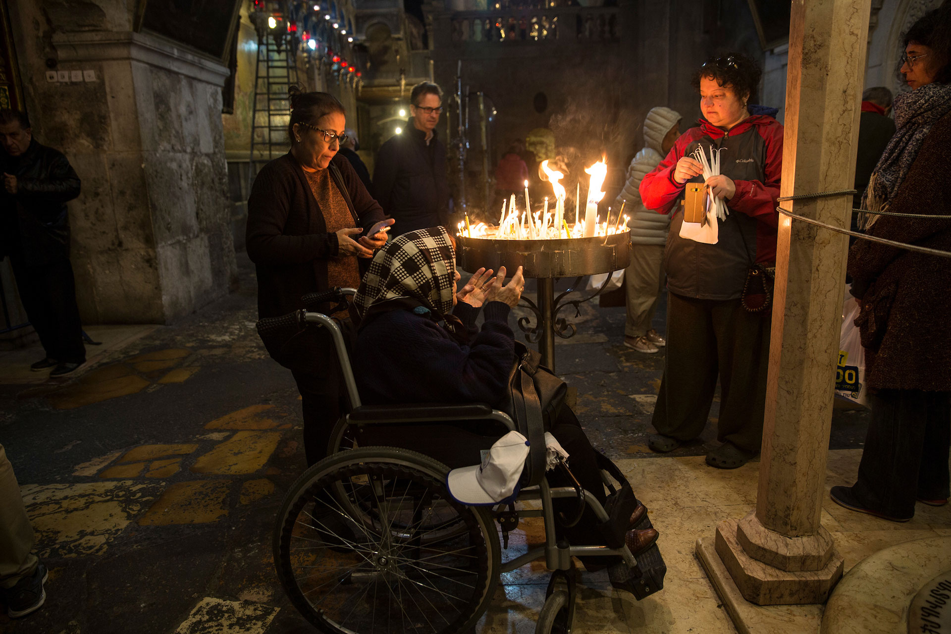 Iraqi Christians Ester Shair ,82, is seen in her wheel chair as she visits the Church of the Church of the Holy Sepulchre in the Old City of Jerusalem during Good Friday on April 30,2018.The family left Baghdad after the Gulf War and some family members emigrated to the United States and Ester and her daughter moved to Australia. (Photo by Heidi Levine for The GroundTruth Project)