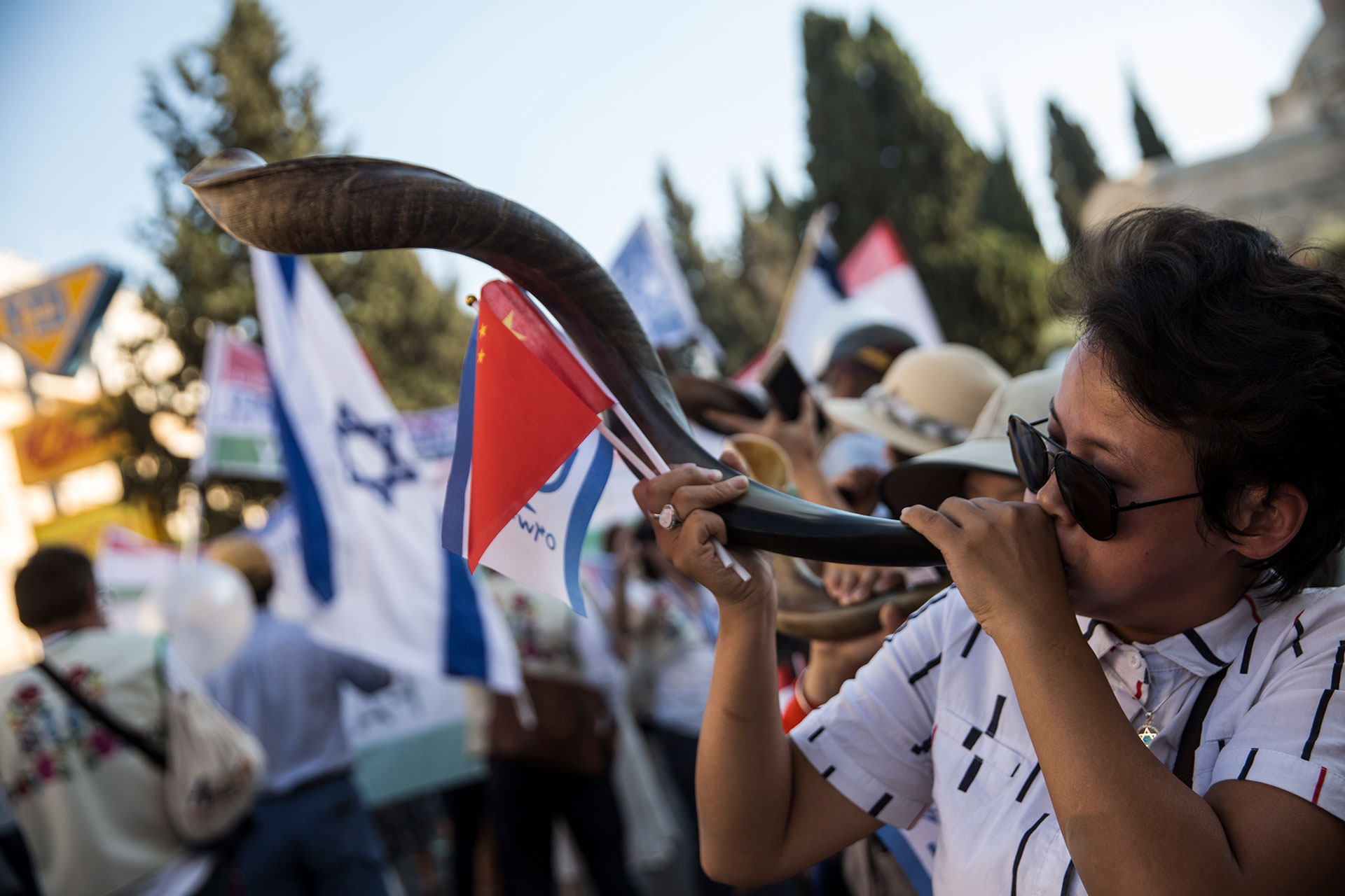A Christian pilgrim from China blows a Shofar during a parade in Jerusalem on September 27,2018. Thousands of Christians from around the world participated in the march which was one of the major events of the week long Feast of Tabernacles festival also known as Sukkot. (Photo by Heidi Levine for The GroundTruth Project).