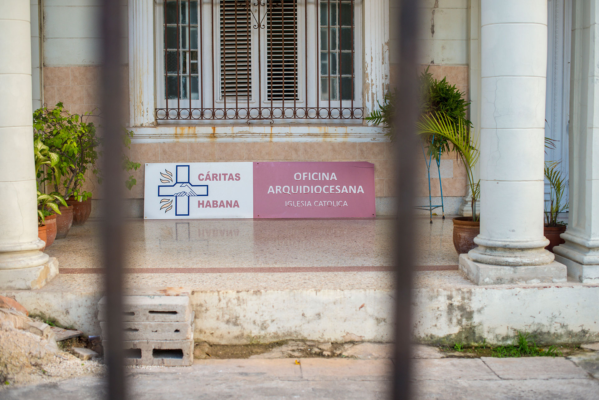 A sign at Caritas Habana is pictured March 7, 2019, in the Vedado neighborhood of Havana, Cuba. Volunteers in Boston, Massachusetts, provide a significant amount of funding to its parent organization, Caritas Cubana, which provides community-based programs and aid throughout the country. (Photo by Estelle De Zan/GroundTruth)
