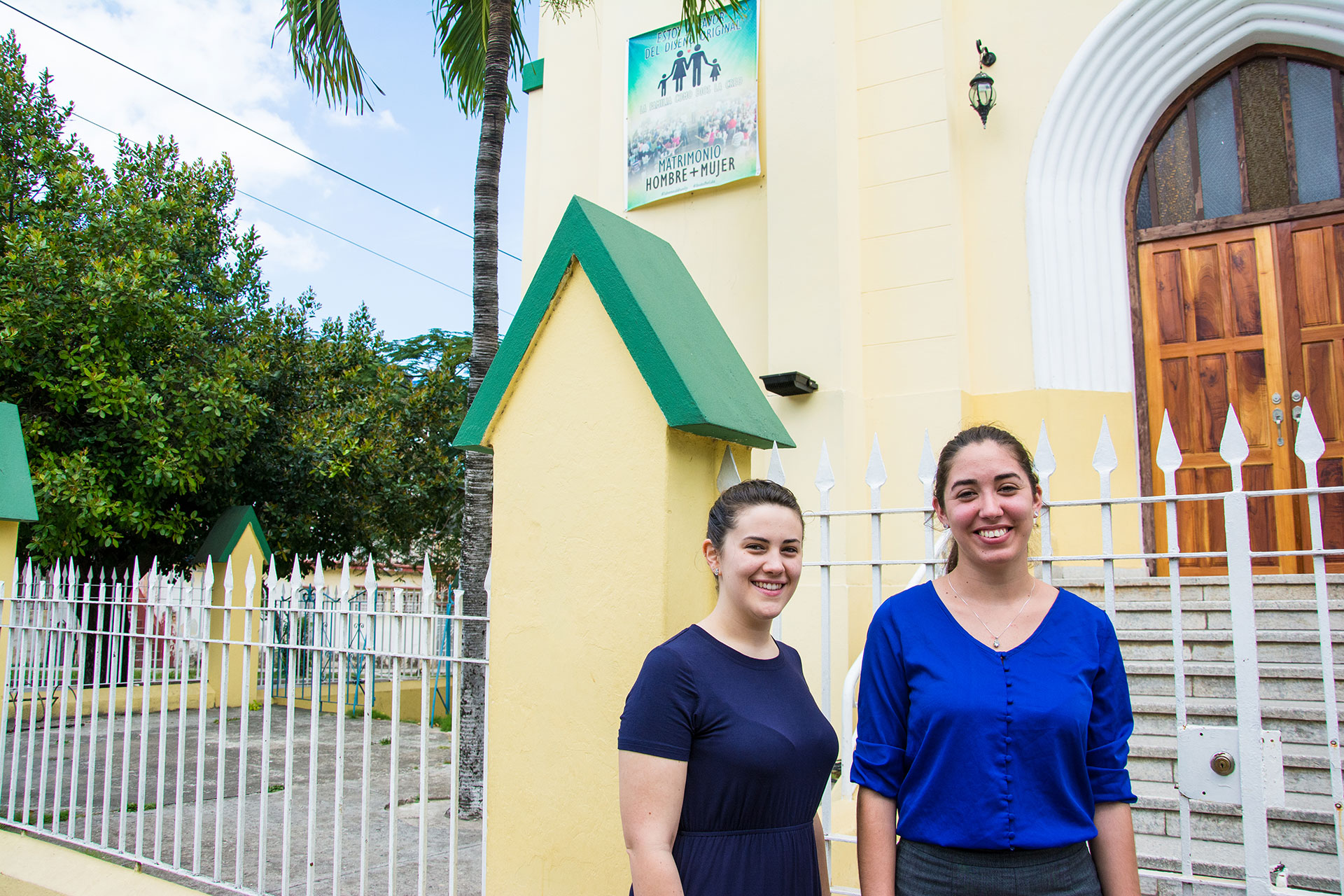 "Danielle Byerly, left, a visiting missionary from Asheboro, North Carolina, and Pastor Leidy Guerra pose for a portrait March 9, 2019, outside of Iglesia Metodista de Marianao, their church in southwest Havana, Cuba. Evangelical churches across Cuba hung posters opposing the constitutional referendum and same-sex marriage with the phrase, ""I am in favor of the original design.""  (Photo by Story Hinckley/GroundTruth)"