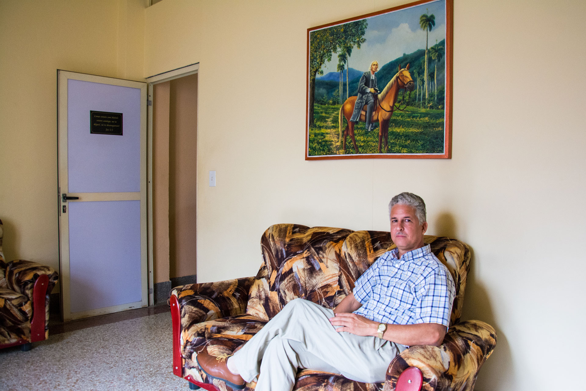 Rev. Enoel Gutierrez poses for a portrait March 6, 2019, at Seminario Evangelico Metodista in Havana, Cuba. Gutierrez commissioned a painting for his office of the Methodist leader from the 18th century, John Wesly, on horseback in Cuba. Rev. Gutierrez is part of the country's growing evangelical community. (Photo by Story Hinckley/GroundTruth)