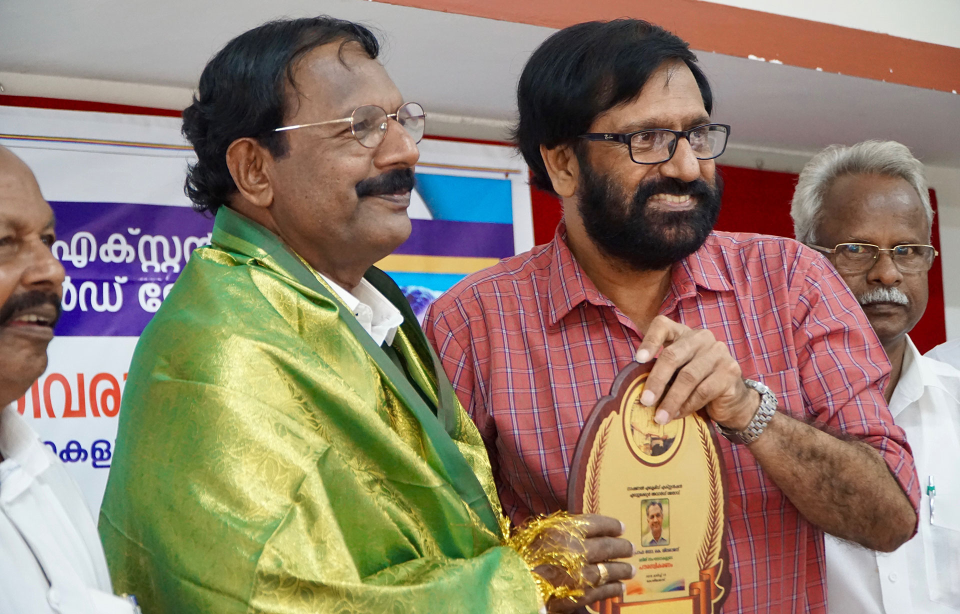 K.P. Ramanunni presents an award to K. Sivaraj, a Dalit education reformer. (Photo by Krishna Narayanamurti)