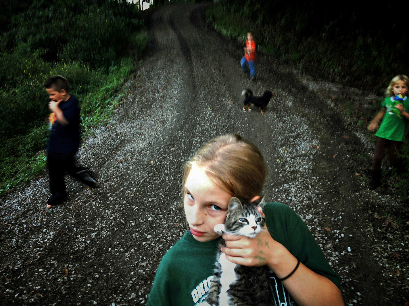 Sonya holds her neighbor's cat next to her grandmother's home. (Photo by Maddie McGarvey)
