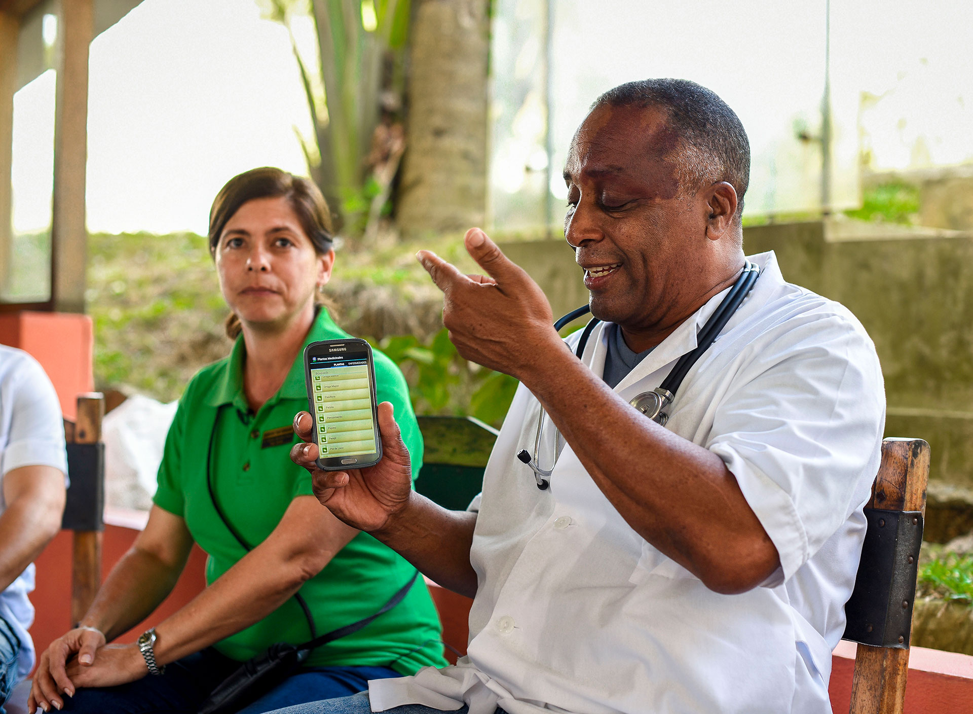 Dr. Rodobaldo Pedroso (right) demonstrates a smartphone app compiling names and uses of medicinal plants next to Idalmis Pe'rez (left) at Las Terrazas on March 3, 2019. The app is one example of traditional medicine's place in Cuba's culture amid technological advancements. (Photo by Estelle De Zan/GroundTruth)