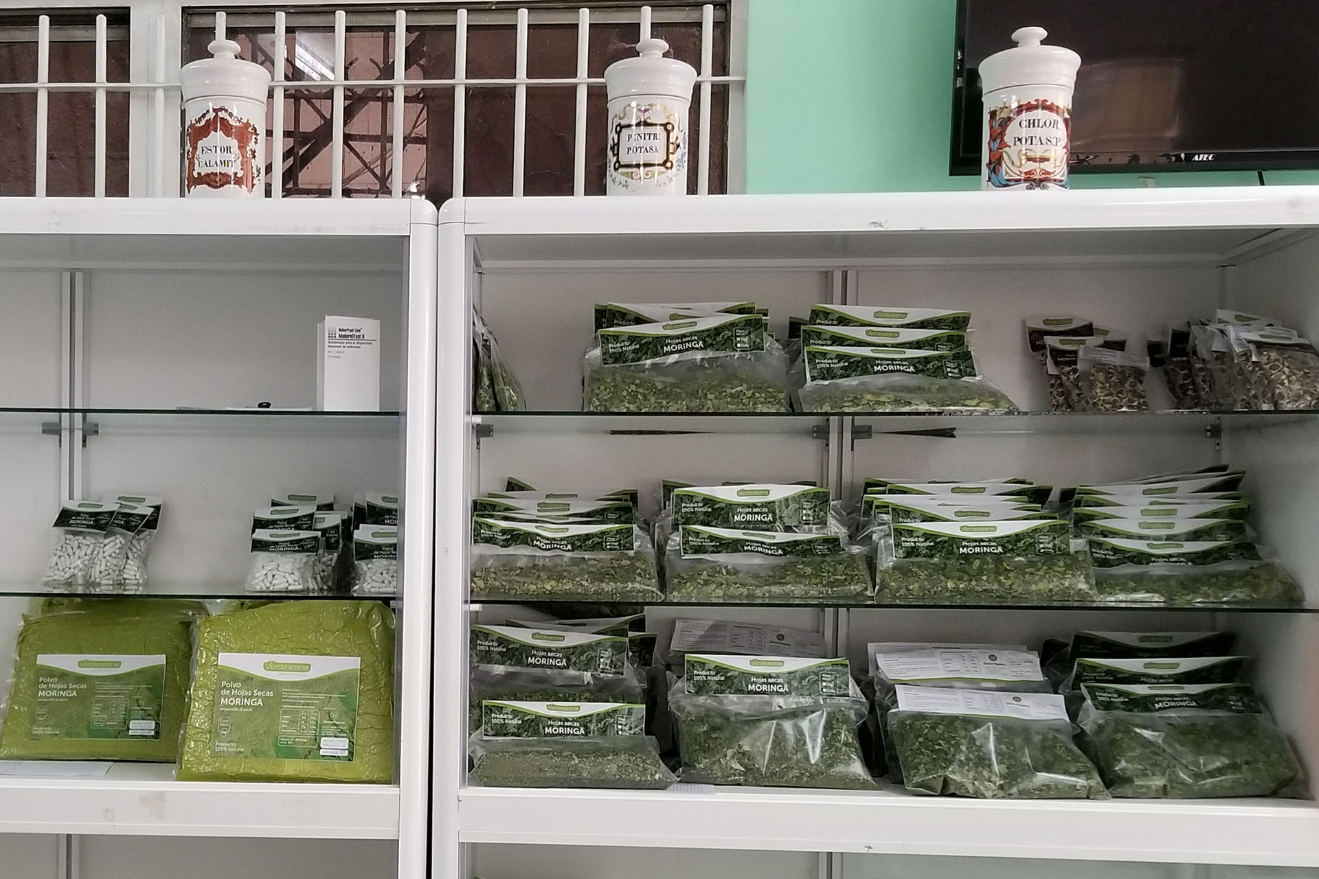The shelves of this pharmacy are stocked with various forms of moringa, including dried leaves and leaf powder, on March 9, 2019. Moringa is one of the most common and versatile plants within the practice of traditional medicine.(Photo by Seamus McAvoy/GroundTruth)