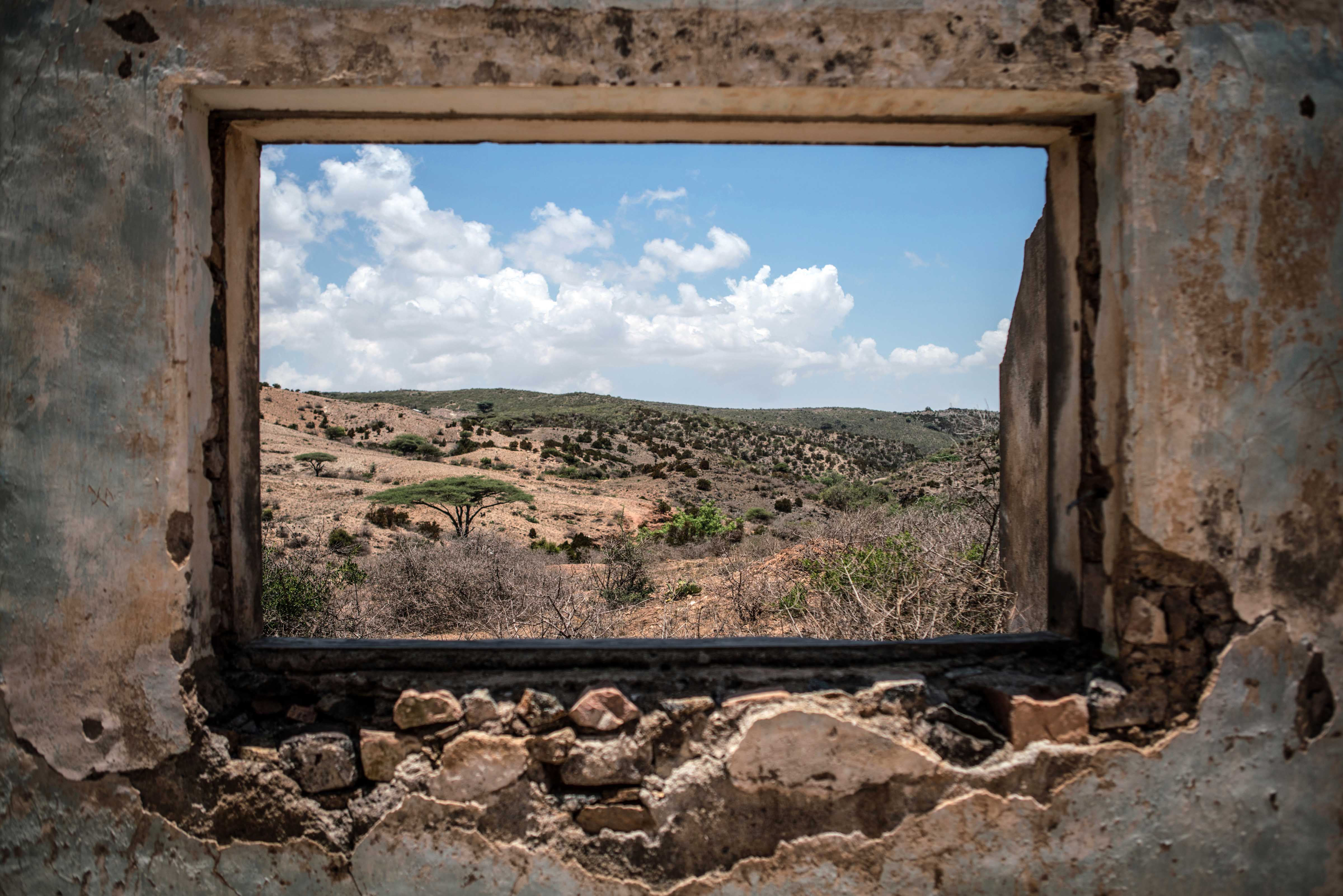 """Somalia's arid landscape as seen from inside a decaying colonial building in the Somaliland town of Sheikh on April 12, 2016. Somalia has never been a forgiving place. A land of extreme temperatures and little rain, the country has faced cyclical droughts and periodic famines throughout the past century. But decades of civil war, coupled with the effects of climate change, have set the country on a path to environmental disaster. Home to a bloody Islamist insurgency that is arguably the world's first climate war, Somalia is grappling with rapid desertification, increasingly erratic rainfall, and the destruction of coastal waters by foreign fishing fleets. """"With this weather pattern, Somalia or Somalis will not survive,"""" says Fatima Jibrell, a Somali-American environmental activist. """"Maybe the land, a piece of desert called Somalia, will exist on the map of the world, but Somalis cannot survive."""" (Photo by Nichole Sobecki/GroundTruth)"""