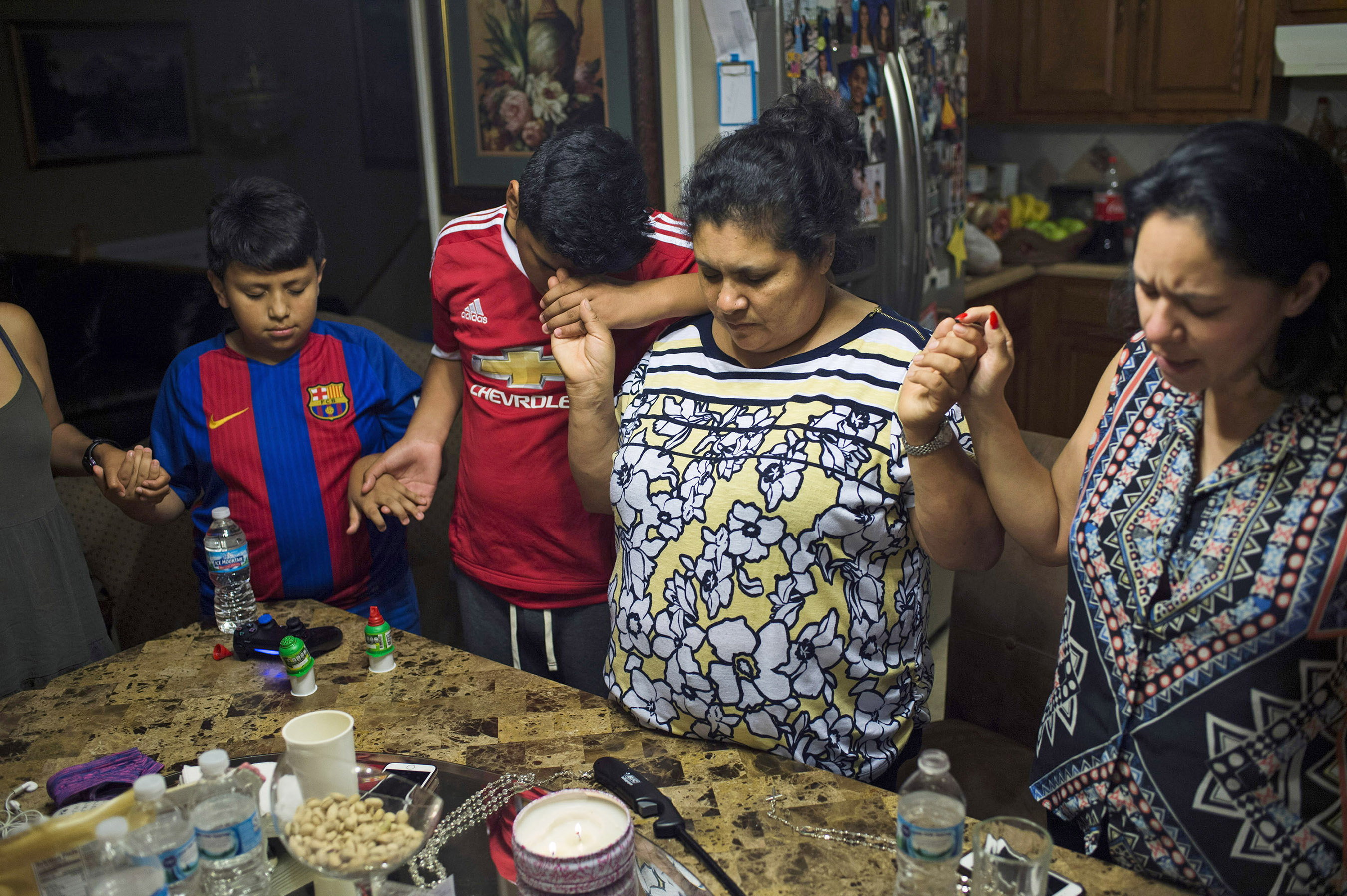 From left, Wilmer Garcia, Bryan Quintana-Salazar, 13, Lourdes Salazar Bautista and Tania Garcia Ortega prayed that Bautista would not face deportation the next morning, on Sunday, July 30, 2017 at Bautista's former home in Ann Arbor, Mich. Bautista gathered around the table with her friends, family and anti-deportation campaign leaders the night before Bautista met with U.S. Immigration and Customs Enforcement (ICE) and confirmed her deportation order. (Photo by Rachel Woolf/GroundTruth)