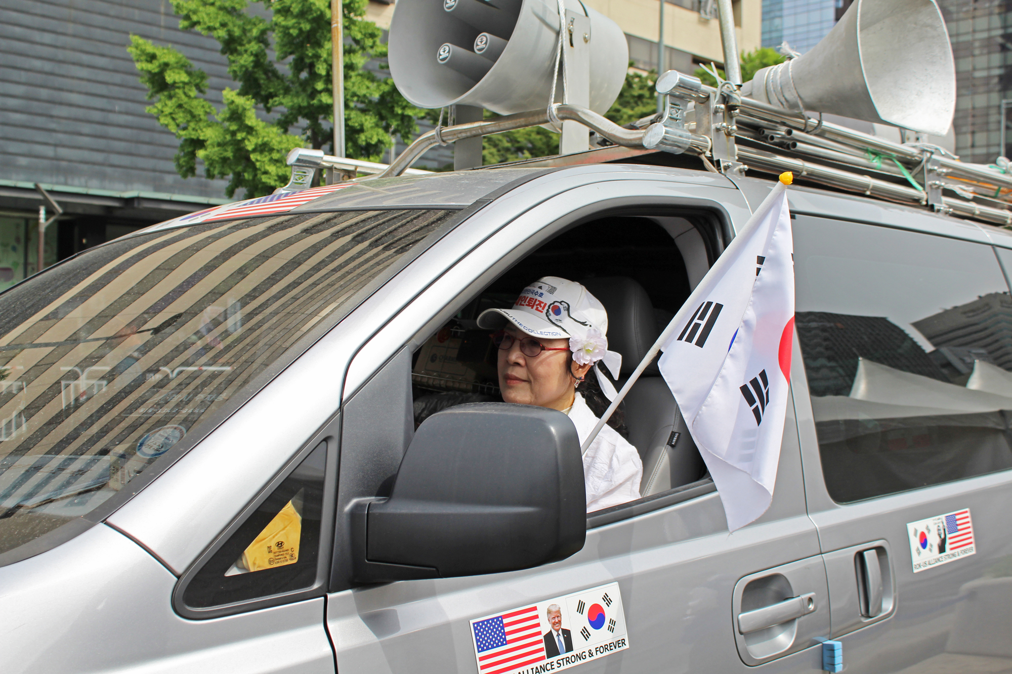 A woman drives a vehicle leading a group of demonstrators protesting for a stronger U.S.-South Korea alliance and less engagement with North Korea on June 1, 2019. (Photo by Kelly Kasulis/GroundTruth)