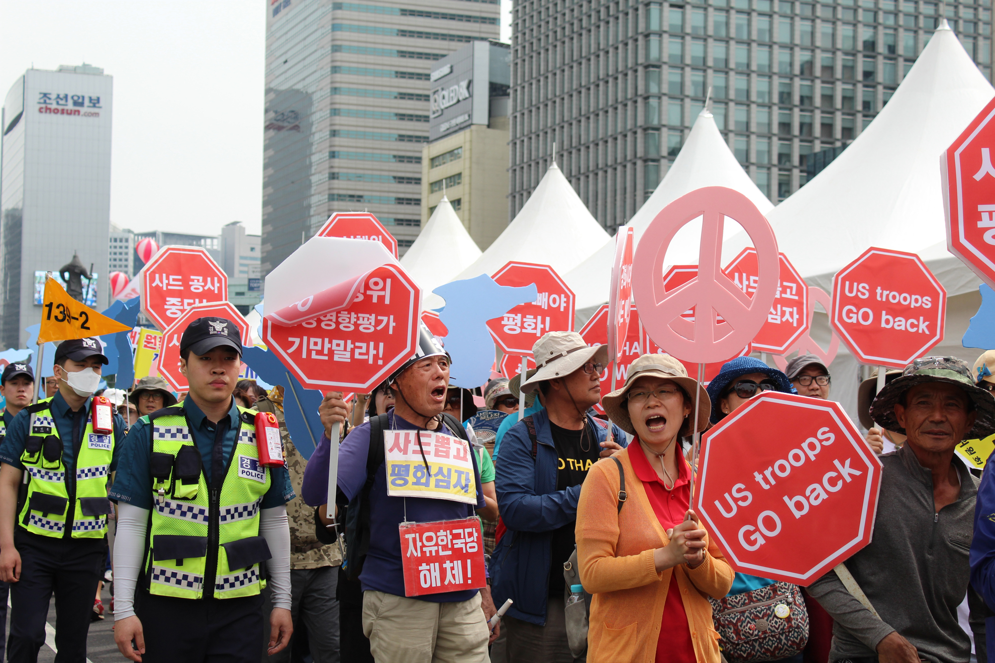 South Korean protestors calling for further engagement between the U.S. and North Korea march through Seoul on June 1, 2019. Several demonstrators hold up signs calling for a withdrawal of U.S. troops from South Korea and the end of the United States' THAAD missile-countering program, which has been a point of tension between the two Koreas, China and the United States. (Photo by Kelly Kasulis/GroundTruth)